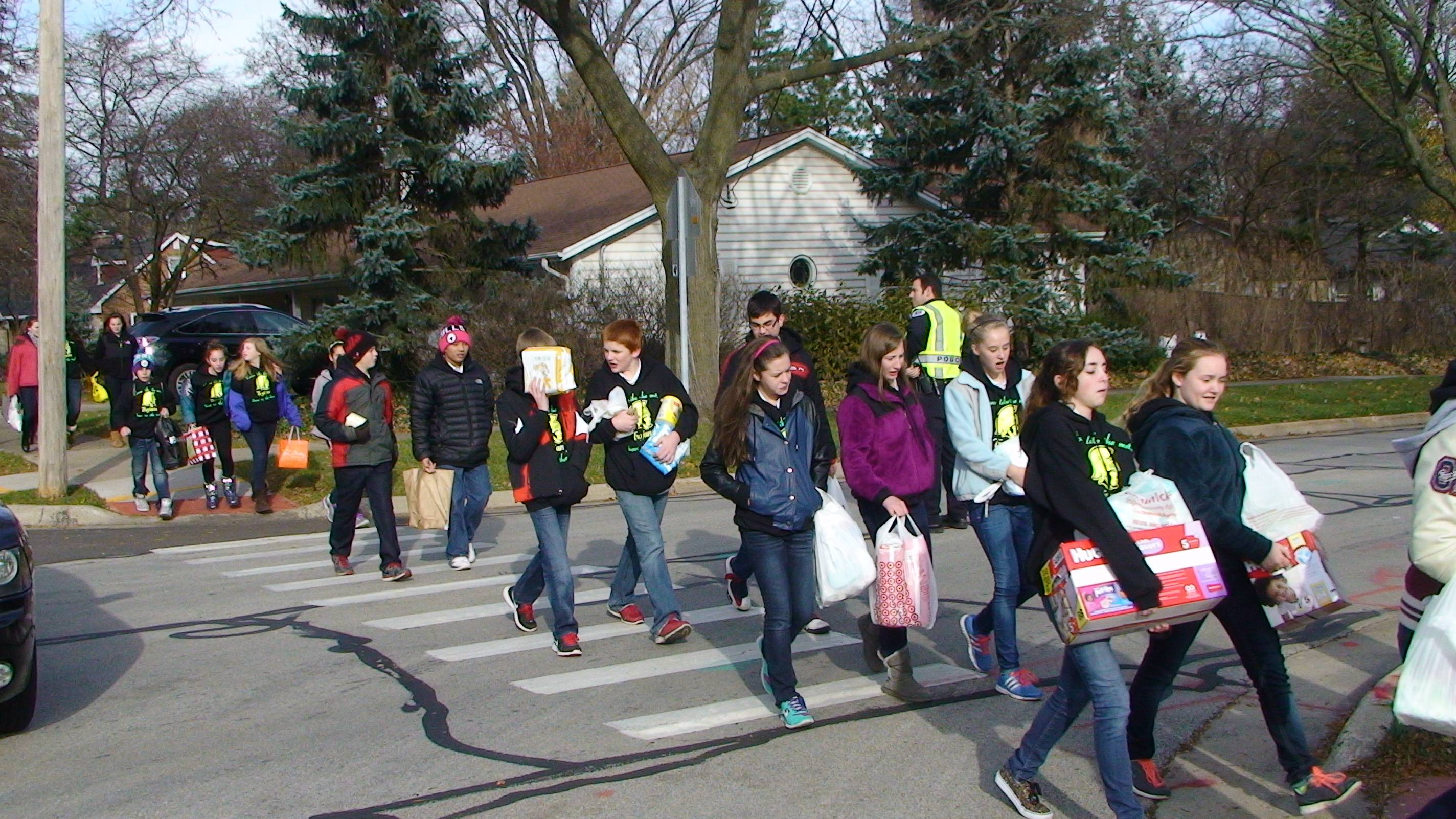 St. Theresa students and teachers walking through the streets of Palatine carrying donations to PHD's Baby & Maternity Closet