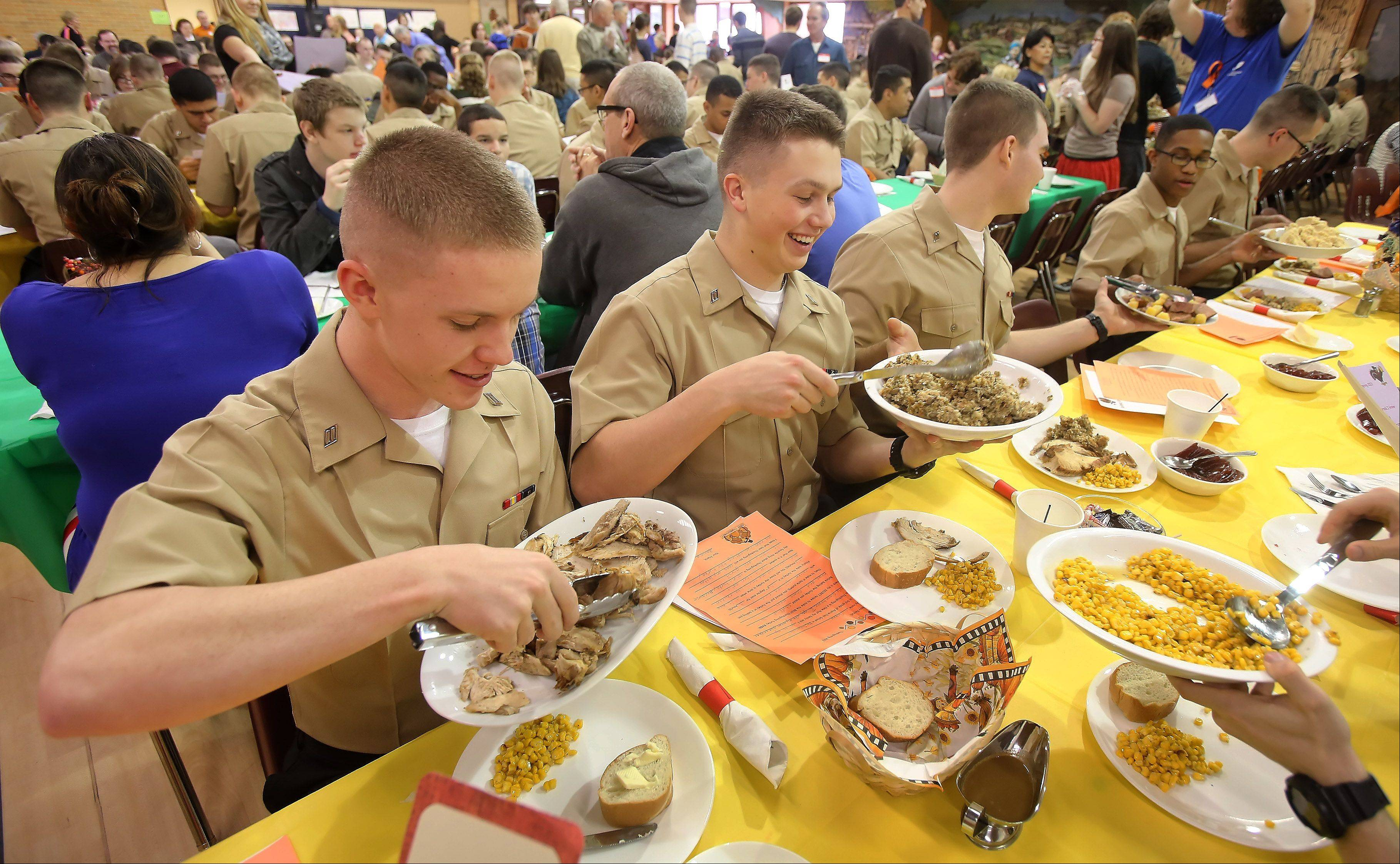U.S. Navy Seaman Wade Eggert of Reno, Nevada, left, and Craig Bandy of Eagle, Idaho, serve themselves during the annual free Thanksgiving dinner offered by the Gurnee Community Church for sailors and residents of the community. The church hosted 165 sailors from Great Lakes Naval Station and provided them with dinner, recreational activities and a phone to call home.