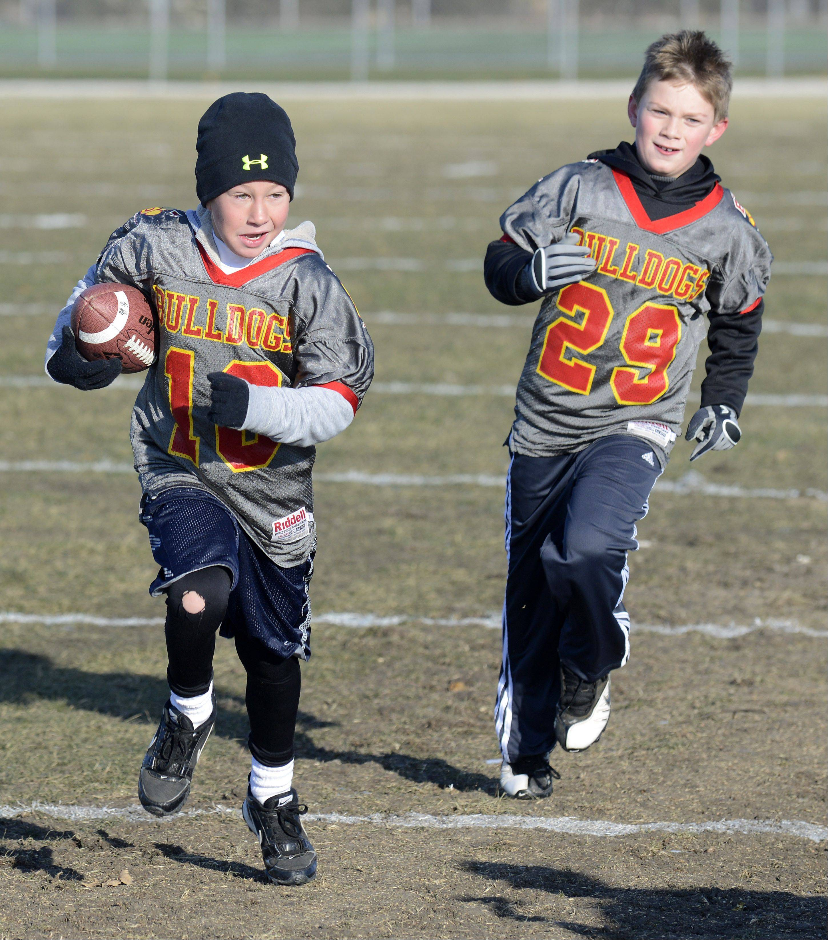 "Danny Moninger, 10, evades a touch ""tackle"" from Dylan Funkhouser, 9, both of Batavia as they warm up before the Batavia Youth Football League's annual Thanksgiving Day Turkey Bowl game. Prior to the game, the youth players cheered on the Batavia High School football team as they practiced in preparation for Saturday's state championship game in DeKalb."