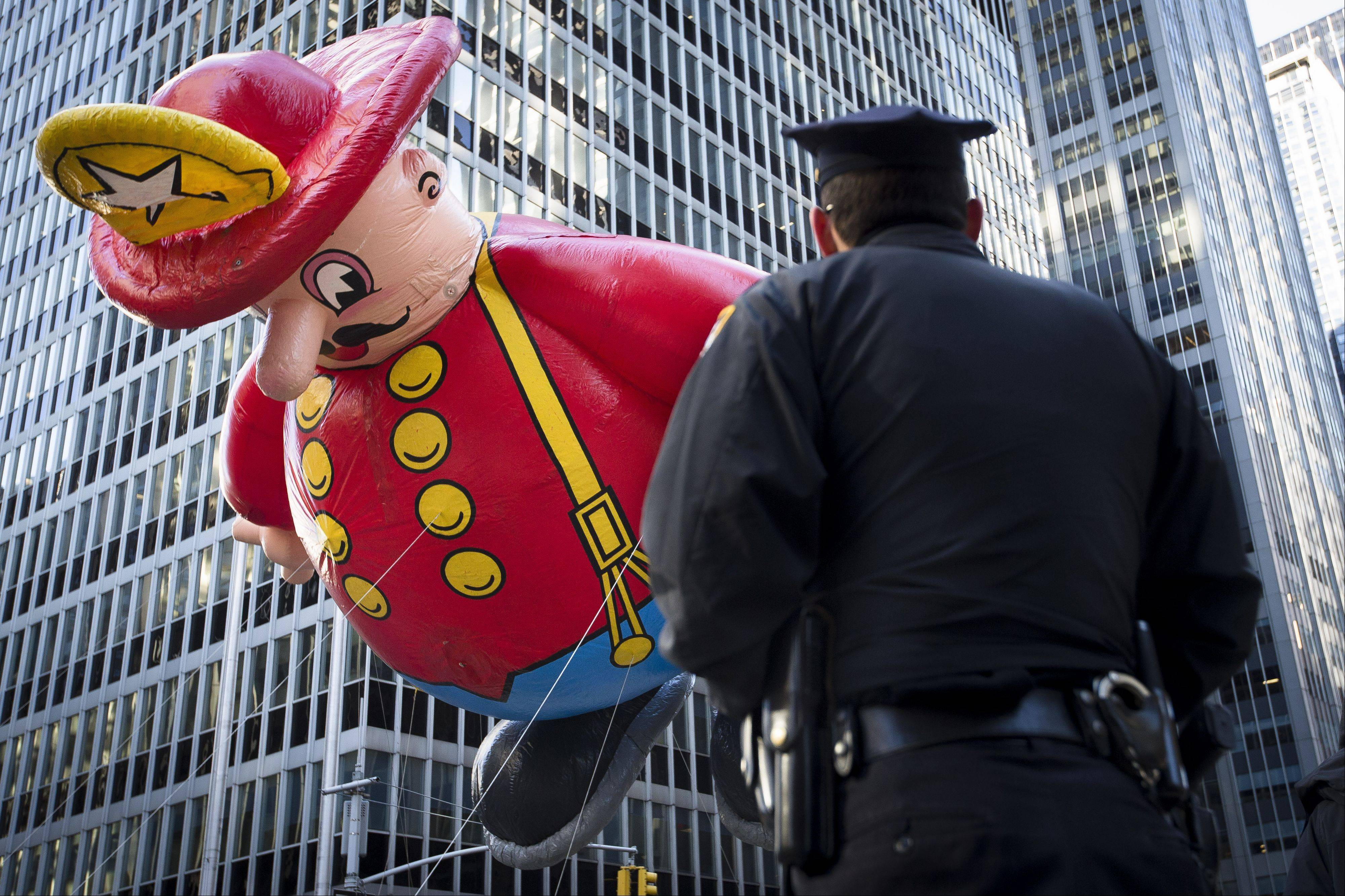A police officer stands on 6th Avenue as a giant fireman balloon passes during the 87th Annual Macy's Thanksgiving Day Parade Thursday in New York. After fears the balloons could be grounded if sustained winds exceeded 23 mph, Snoopy, Spider-Man and the rest of the iconic balloons received the all-clear from the New York Police Department to fly between Manhattan skyscrapers on Thursday.