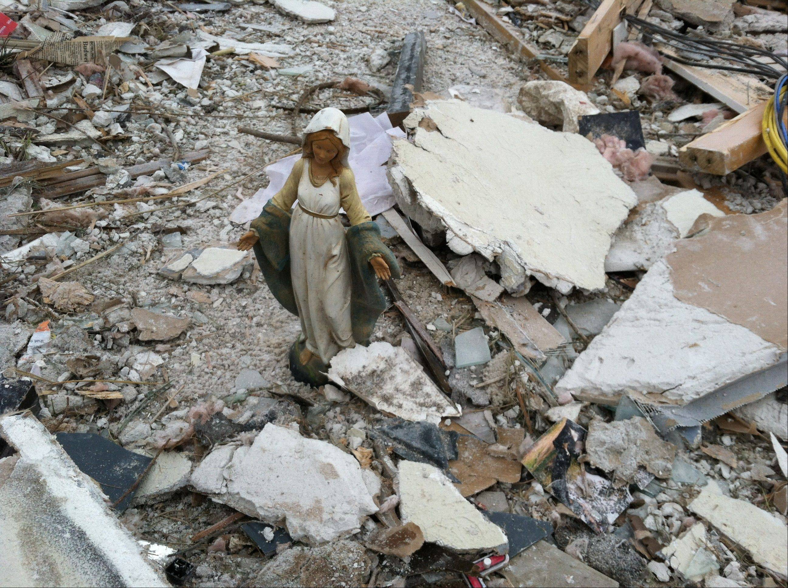 In a November 2013 family photo provided by Annmarie Klein, a statue of the Blessed Virgin Mary stands amid the ruins of the former home of Klein and her family in Washington, Ill., after the Nov. 17, 2013 that destroyed their home. Klein is asking for the publicís help in locating three cards swept away by the twister. The cards were addressed to the three children of Kleinís brother, Paul McLaughlin, who before his 2005 death from colon cancer entrusted Klein to give the cards to his children someday.