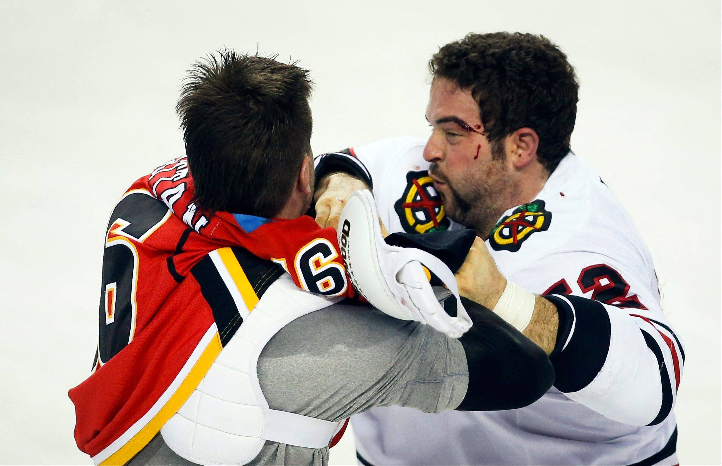 The Hawks' Brandon Bollig, right, scuffles with the Flames' Brian McGrattan during the first period Wednesday in Calgary, Alberta,