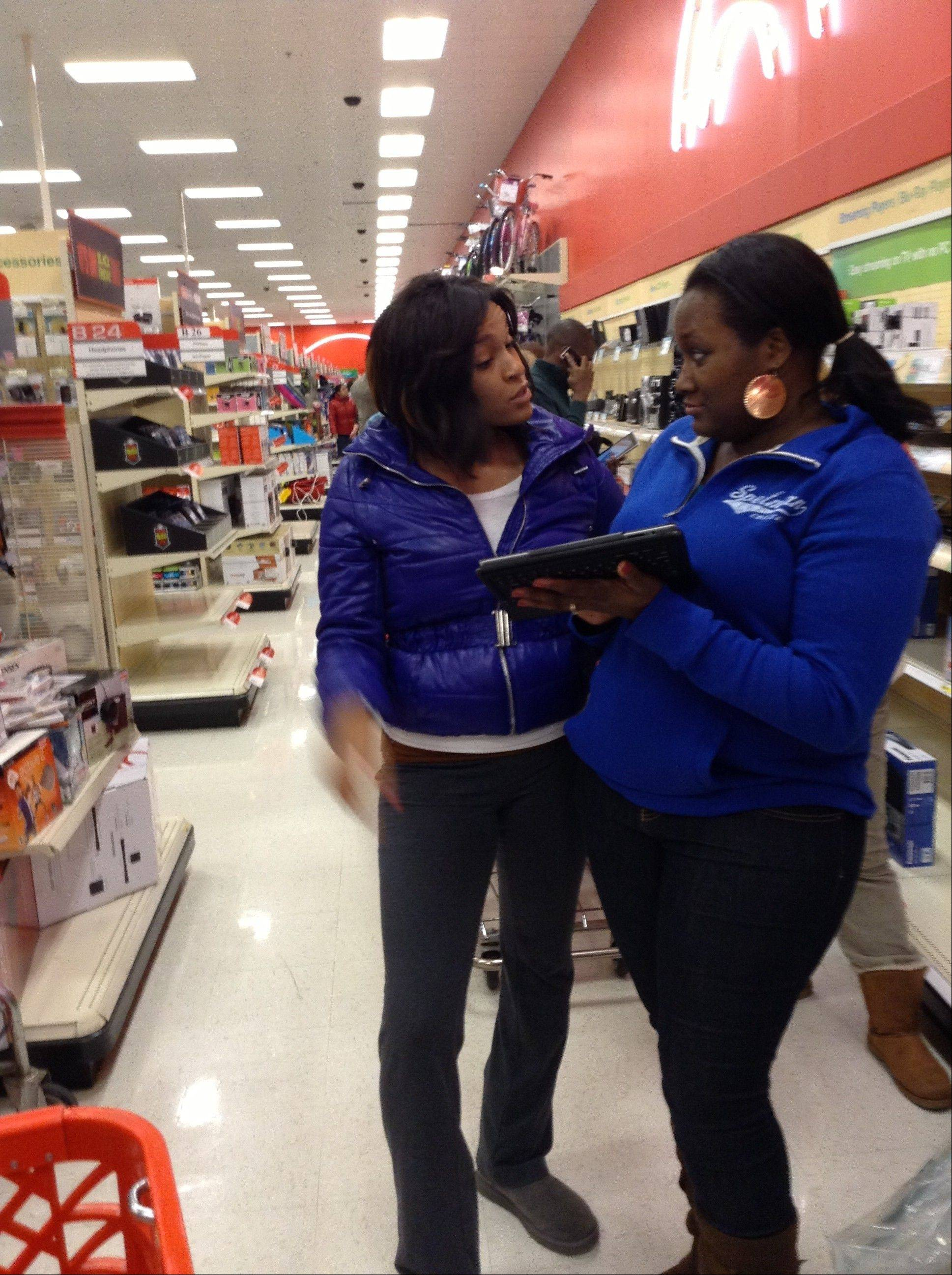 "Devin Hayes, left and Brittney Walker, both of Elgin, share intelligence last year while shopping at a big-box store. The duo, along with about 20 family members, plan on hitting up the holiday sales, starting Thanksgiving Day. ""Your team has to be strong, it has to be fierce,"" Walker said. ""There's one last item left, you've got to be able to go for it and take no prisoners."""