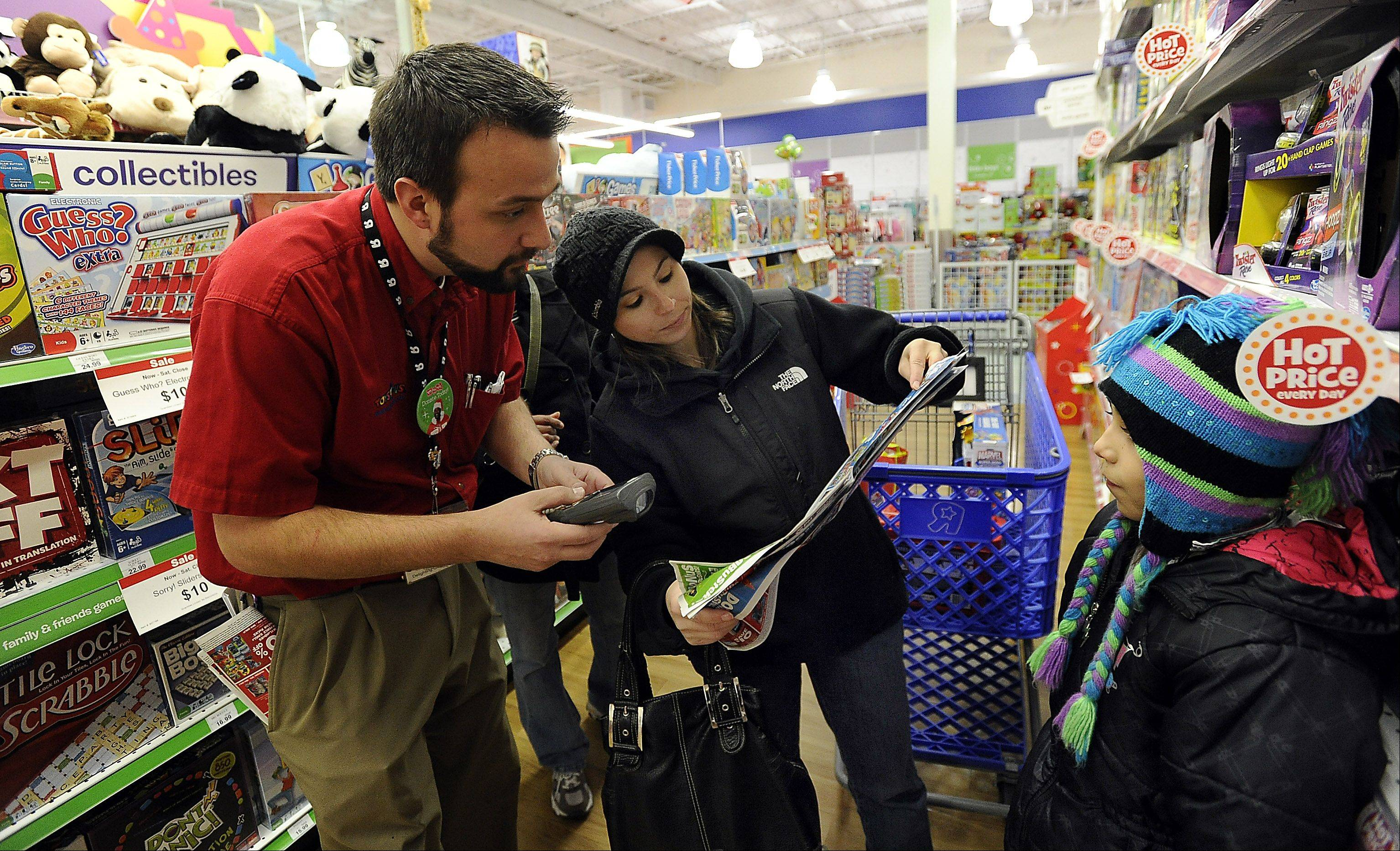 "Scott Demers, assistant manager at the Toys ""R"" Us store in Schaumburg, helps Jennifer Serrano of Roselle, who, with her 9-year-old daughter Alexis, was purchasing gifts for a family who lost their home in last week's tornado in Washington, Ill."