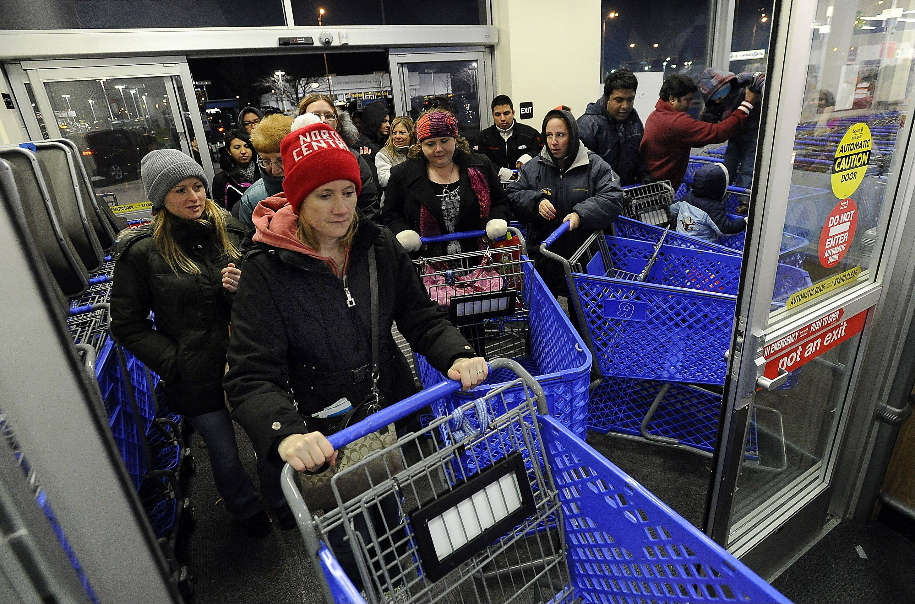 "Sarah Kristh of LaSalle leads the pack of shoppers after the doors opened Thursday night at the Toys""R""Us store in Schaumburg."