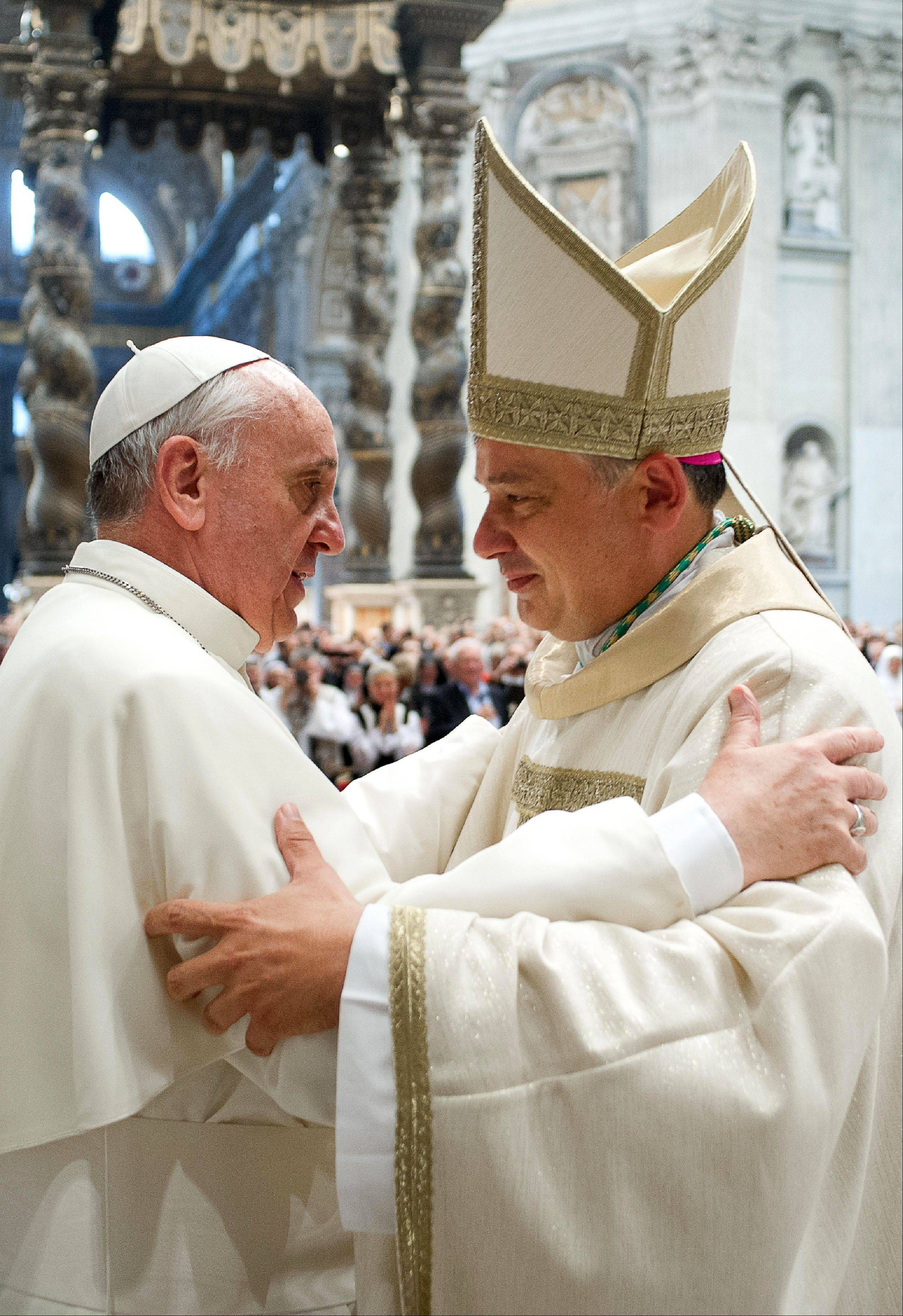 Pope Francis, left, hugs Vatican Almoner, Archbishop Konrad Krajewski, after his episcopal ordination, in St. Peter's Basilica.