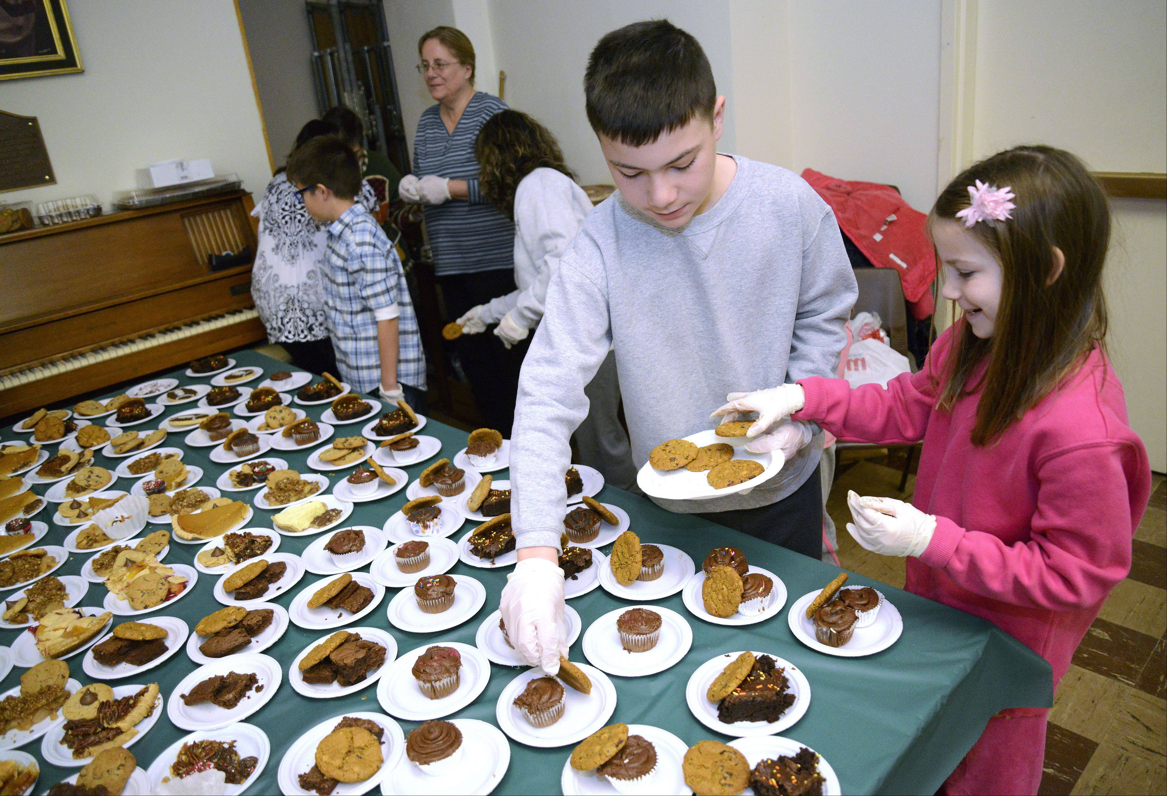 Shane Bonner, 12, of Hoffman Estates, and his sister, Angelina, 10, make dessert plates for the Elgin Community Thanksgiving Dinner at the First United Methodist Church on Thanksgiving Day. Shane and Angelina made brownies and cupcakes themselves to bring to the event. Shane will celebrate his bar mitzvah next year and this was his way to give to the community in preparation.