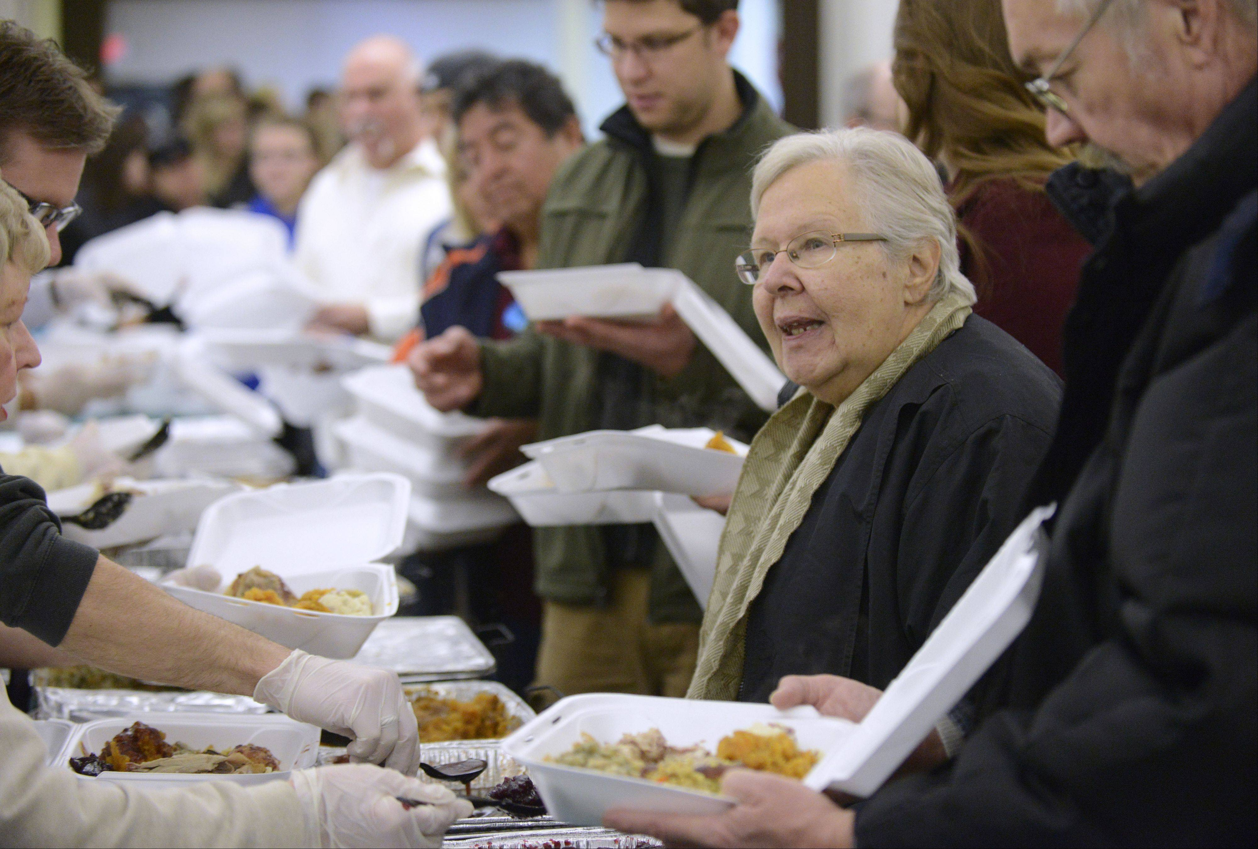 Barb Roderick of Elgin waits in line Thursday as seven turkey dinners are packaged for her at the Elgin Community Thanksgiving Dinner at the First United Methodist Church. Roderick collected names from residents in her building at Burnham Manor (as well as a neighbor who lives down her block) who wanted a hot meal on the holiday and delivered directly to them. Every month she does something to give back to the community and this was her November pick. She even enlisted the help of her neighbor, Larry Funk, right, to help her deliver the meals.