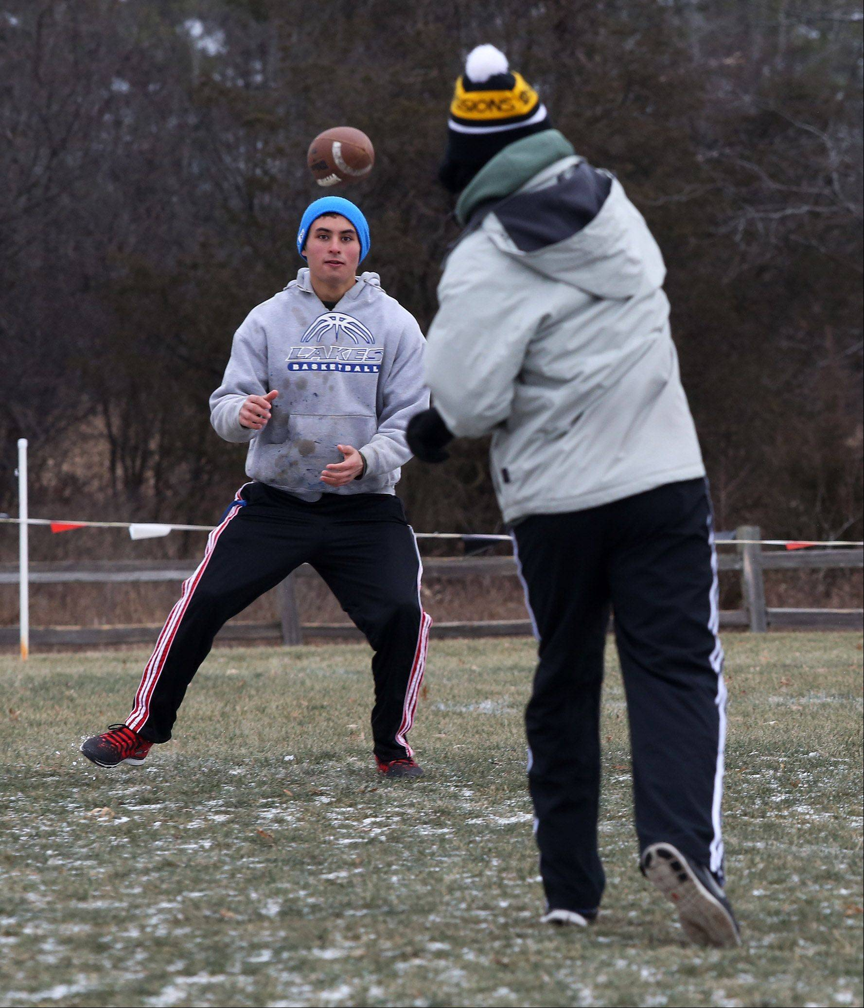 "Evan McCollum catches as pass from Allen Johnson as six friends play a pickup football game after the Lake Villa Township ""Food for Football Turkey Bowl"" event was cancelled at Tiny's Park on Thanksgiving morning. Organizers had hoped to collect food and money for the Lake Villa Township Food Pantry but only one team registered."