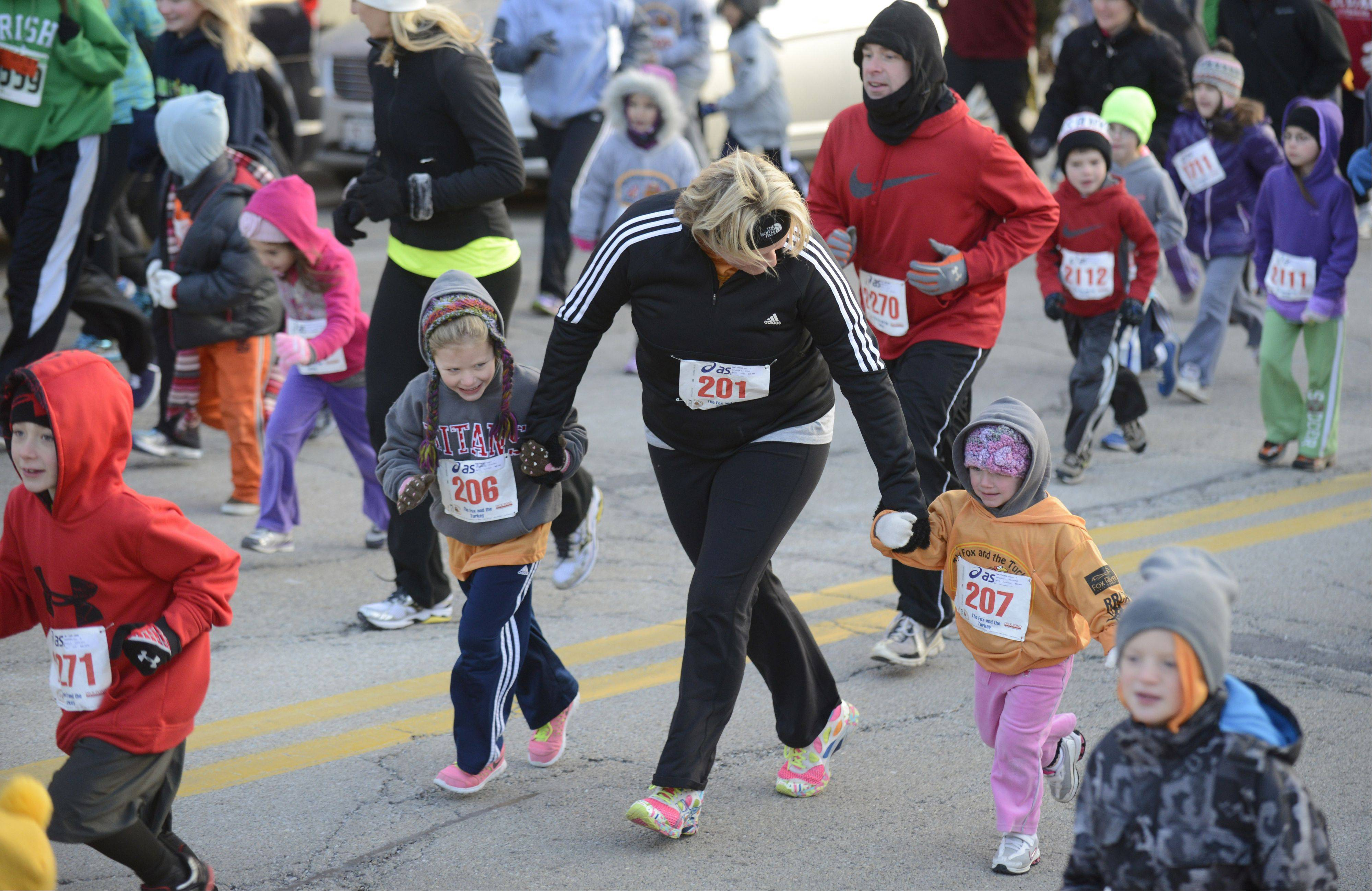 Springfield's Amy Matthews runs with her daughters, Karigan, 6, left, and Addie, 3, in the Youth Mile in the annual Fox and Tureky Races in Batavia on Thanksgiving Day. Matthews grew up in Bartlett and brings her family to visit her parents, Keith and Bev Christensen, now living in Hampshire.