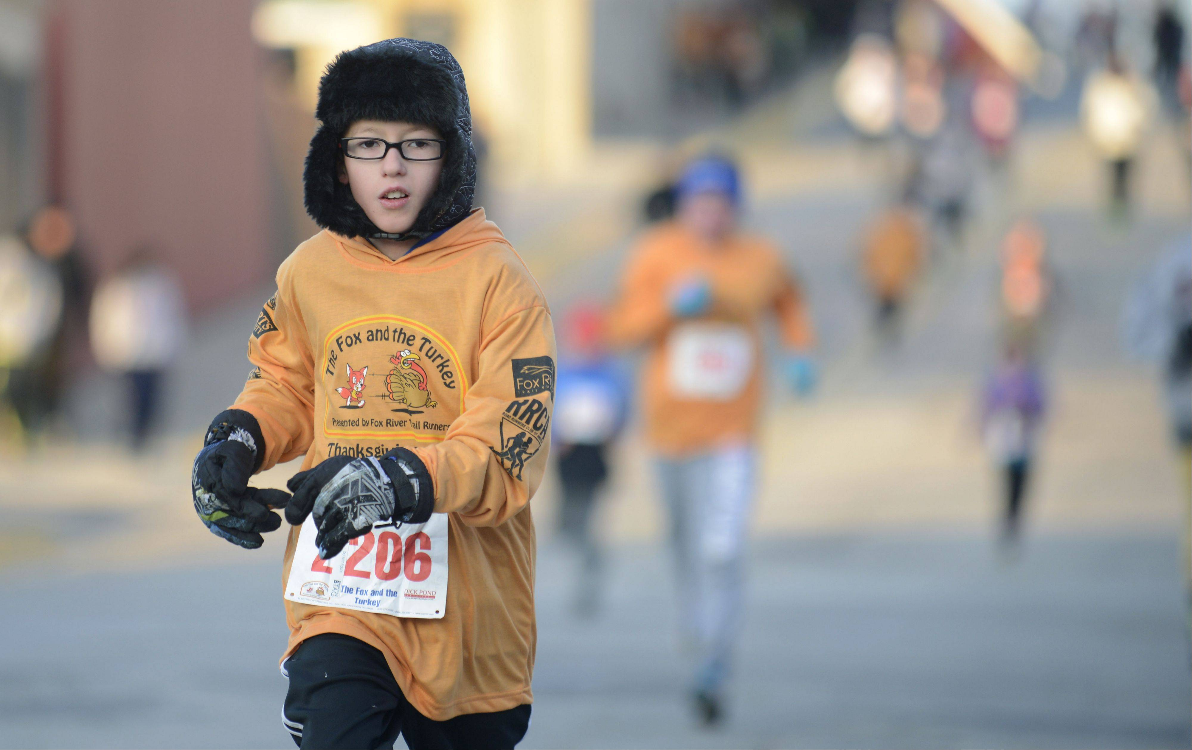 Matthew Conley, 11, of North Aurora nears the finish line of the Youth Mile in the annual Fox and Turkey Races in Batavia on Thanksgiving Day. This is the first year he's run in the event. He was joined by his younger brother, Ethan Potts, 5, as well.