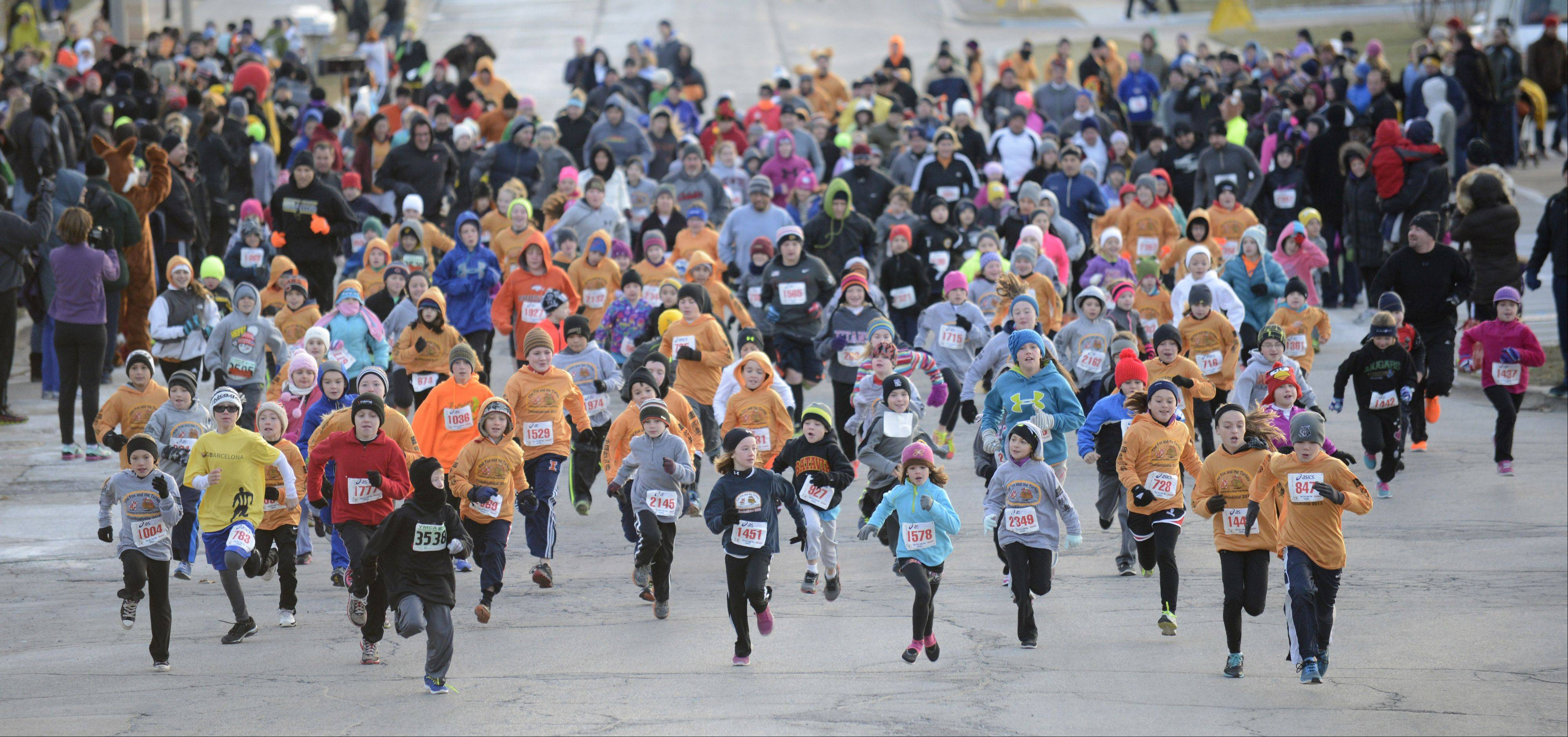 Kids head down Houston Street from the starting line of the Youth Mile during the annual Fox and Turkey Races in Batavia Thursday morning.
