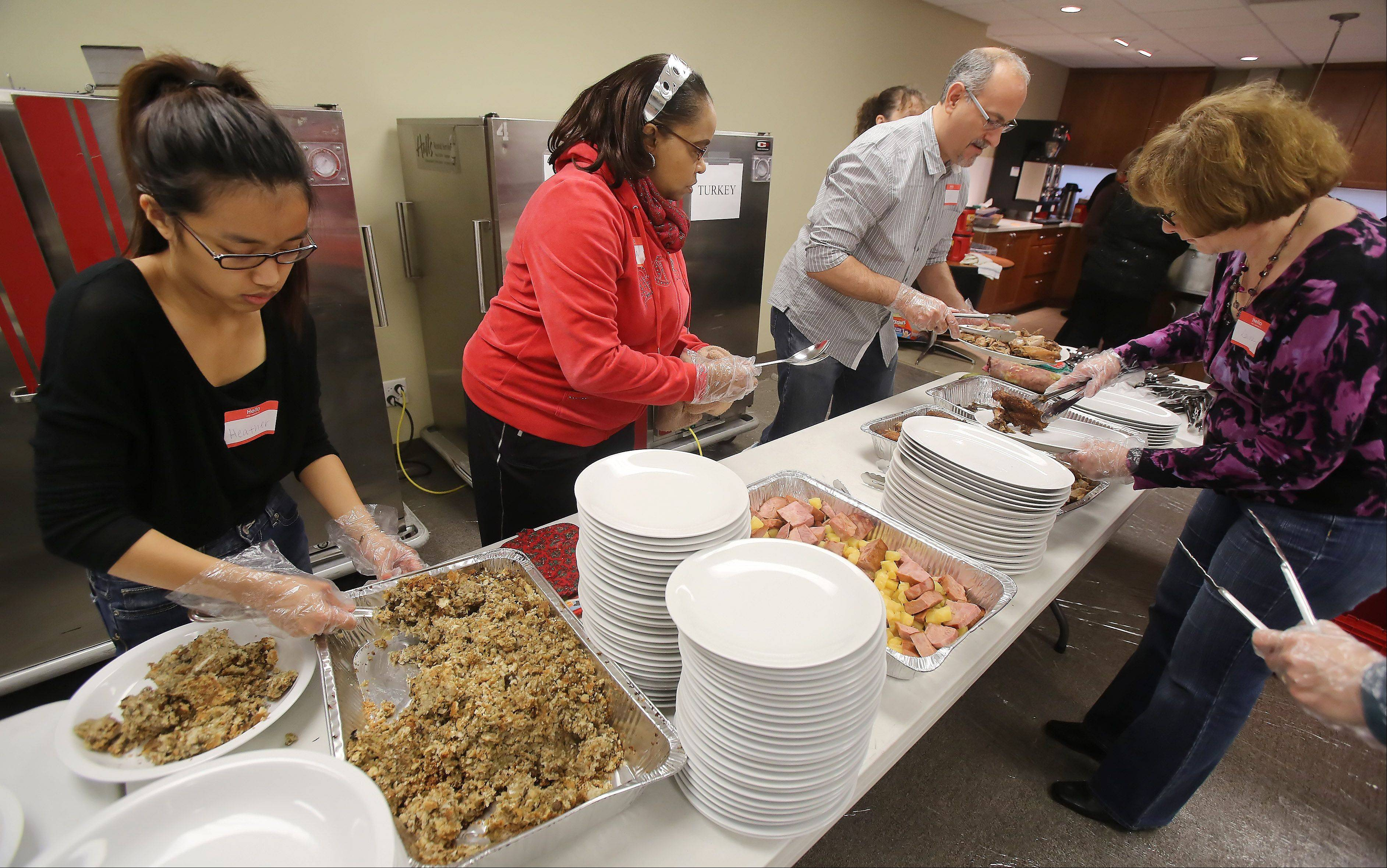 Volunteers dish up platters for the annual free Thanksgiving dinner at the Gurnee Community Church.