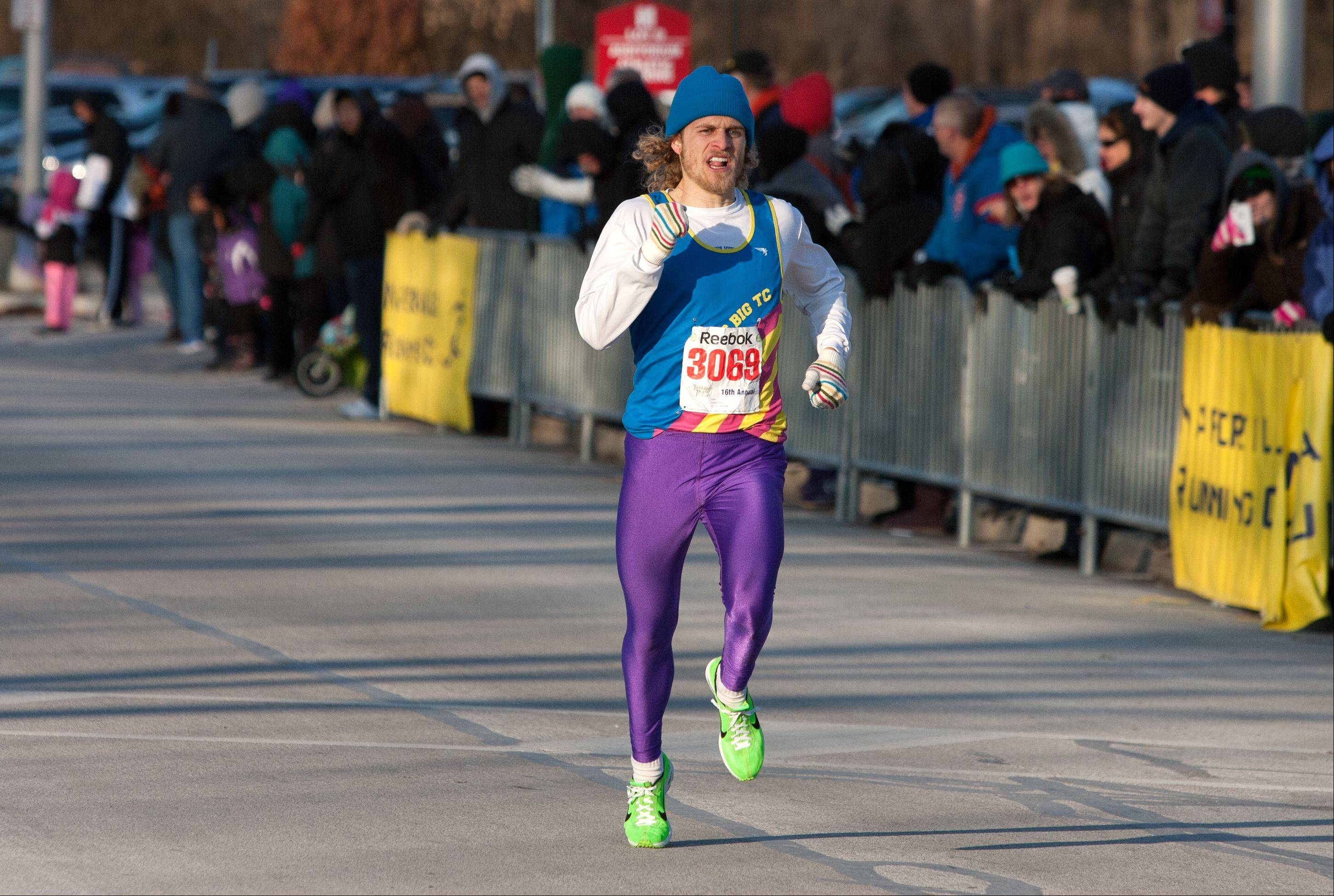 Andrew Nelson, 22, of Geneva finishes first in the 16th annual Naperville Noon Lions 5K Turkey Trot Thanksgiving morning.