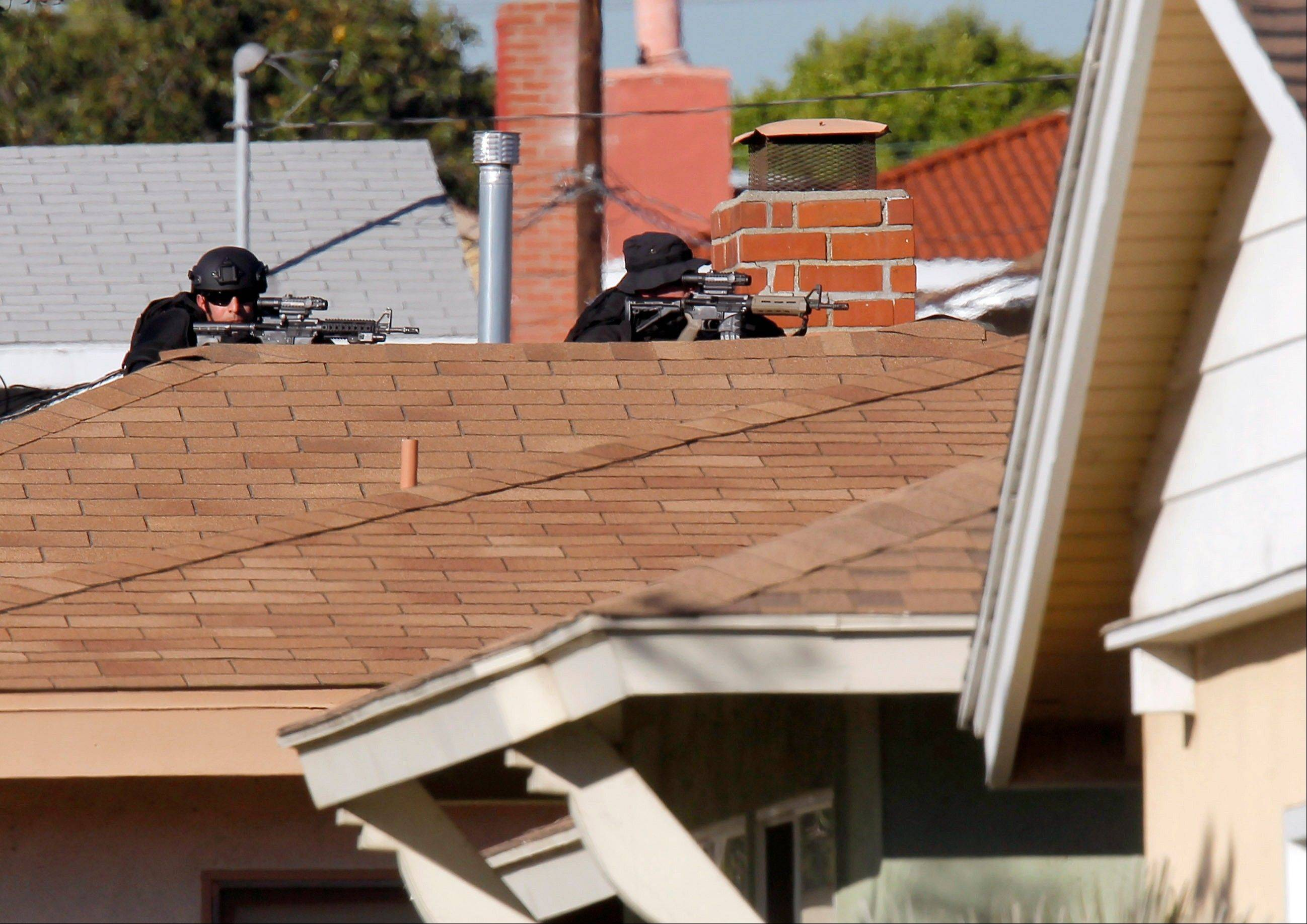 Inglewood police snipers take up a position Wednesday outside a residence where a police officer was shot and another received minor injuries in a confrontation with a gunman.