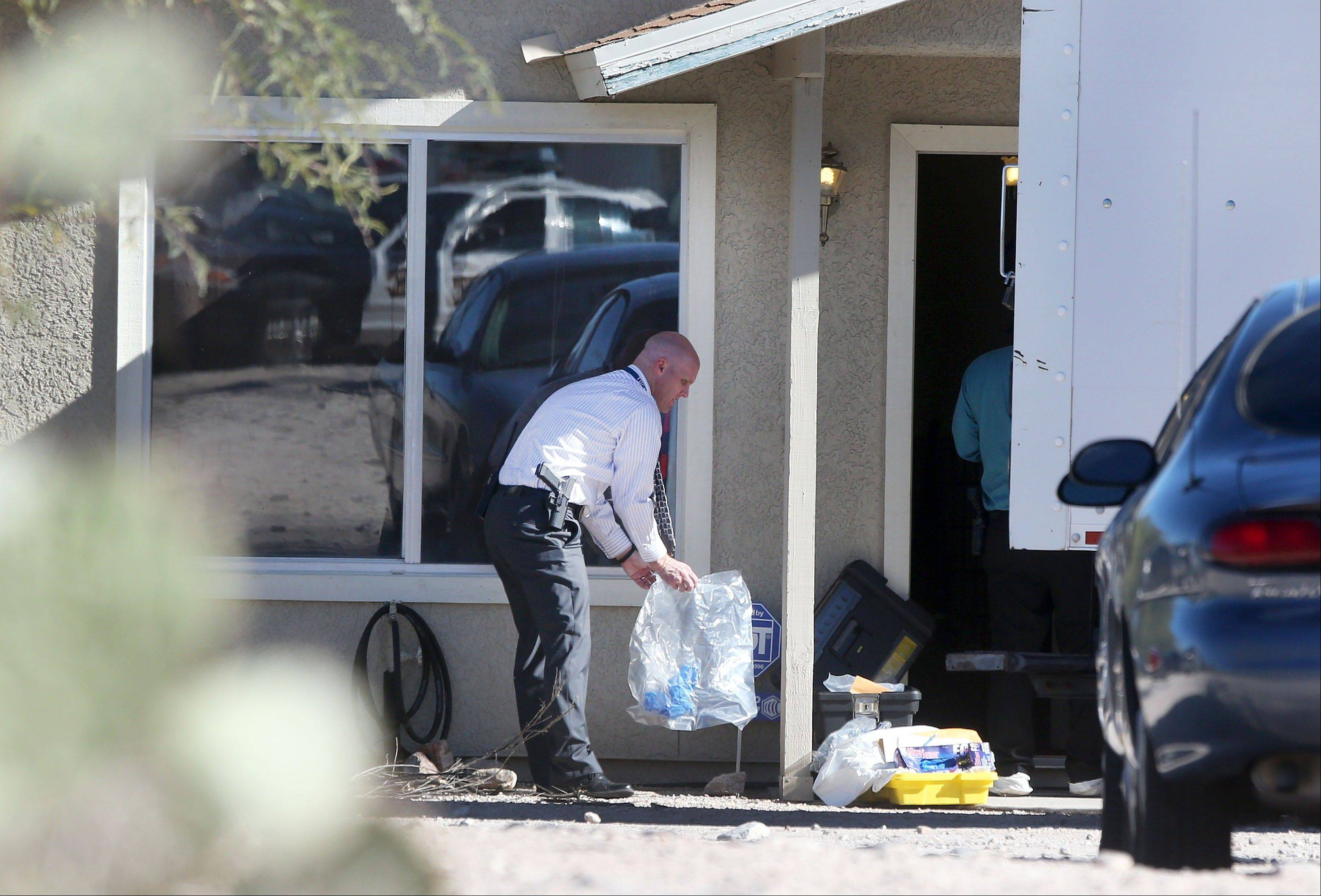 Tucson Police Department investigators and evidence technicians investigate the scene at a home where two people were arrested Tuesday, Nov. 26, 2013, after three girls told authorities that they have been imprisoned for possibly the past two years, in Tucson, Ariz. Tucson police said the girls are siblings � ages 12, 13 and 17 � and their mother and stepfather have been arrested in a case that's being investigated as alleged child abuse and imprisonment.