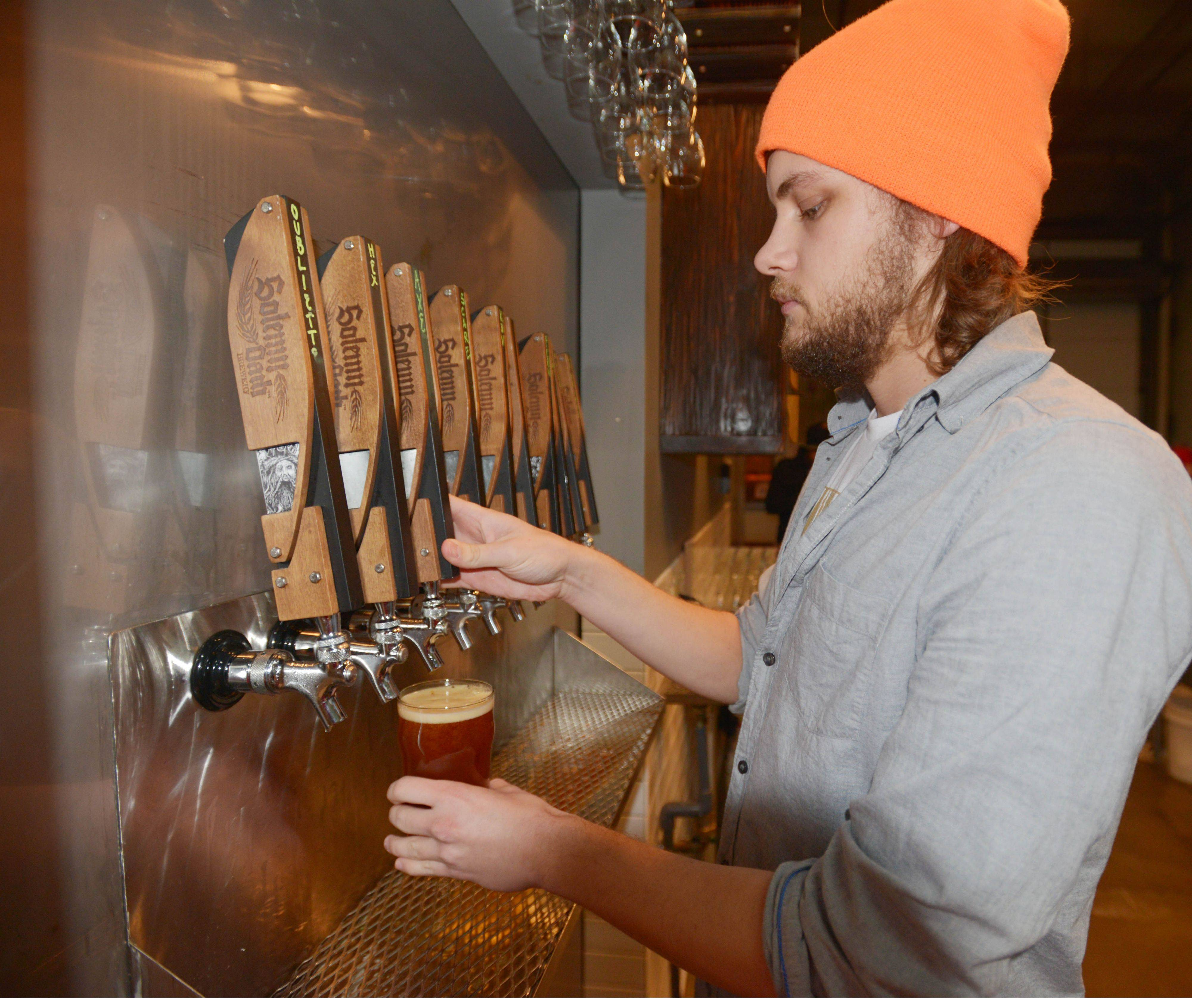 Lou Waldmeir taps a beer at Solemn Oath Brewery in Naperville.