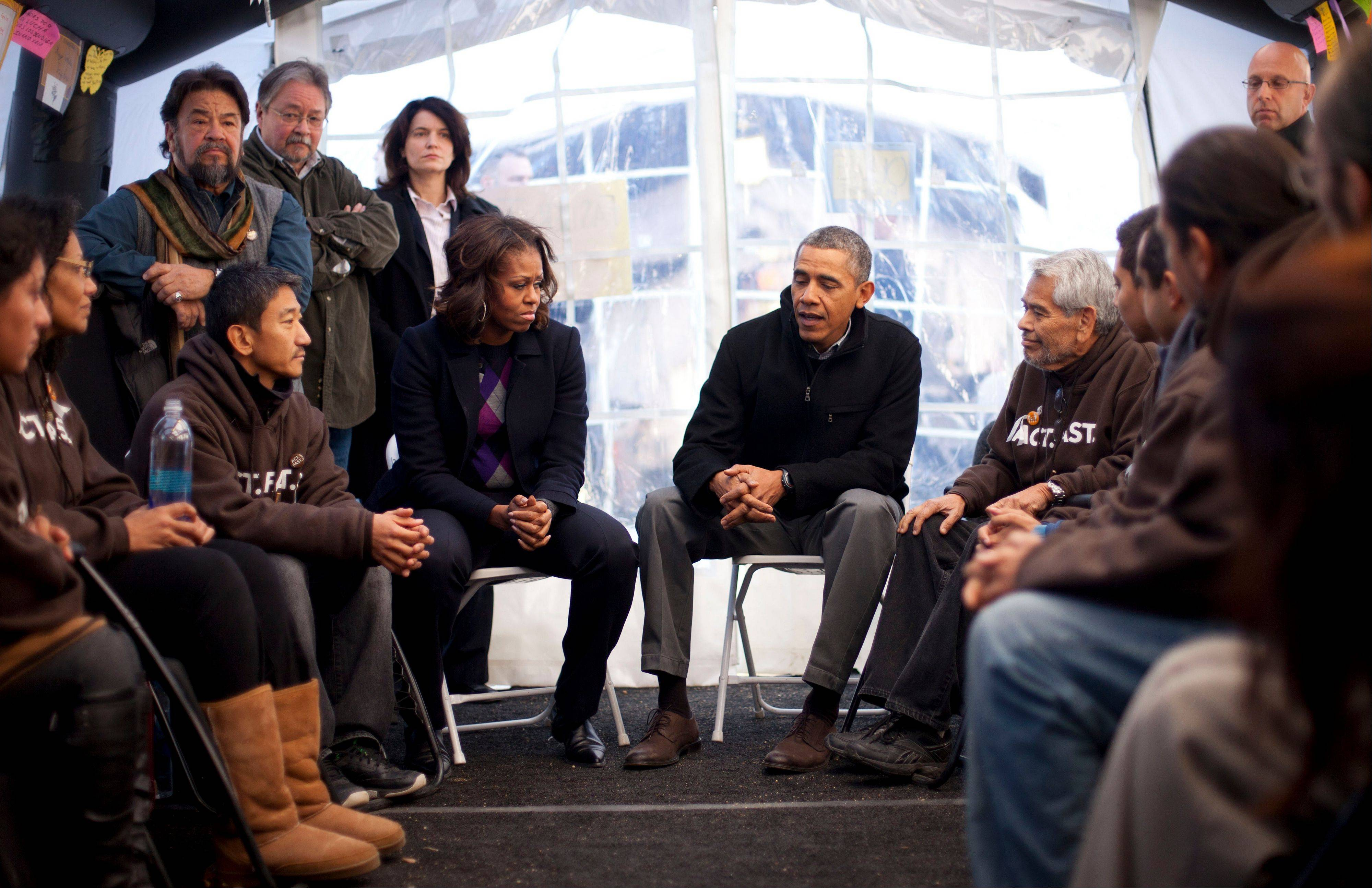 President Barack Obama and first lady Michelle Obama visit Friday with individuals who are taking part in Fast for Families on the National Mall in Washington.