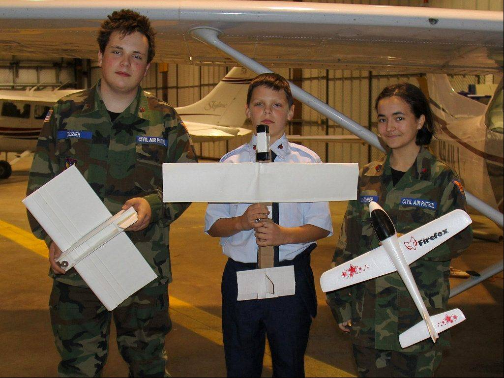 Cadets from the Fox Valley Composite Squadron, shown here displaying their larger paper airplane designs, on Sunday will attempt to break the world record for the highest paper airplane flight.