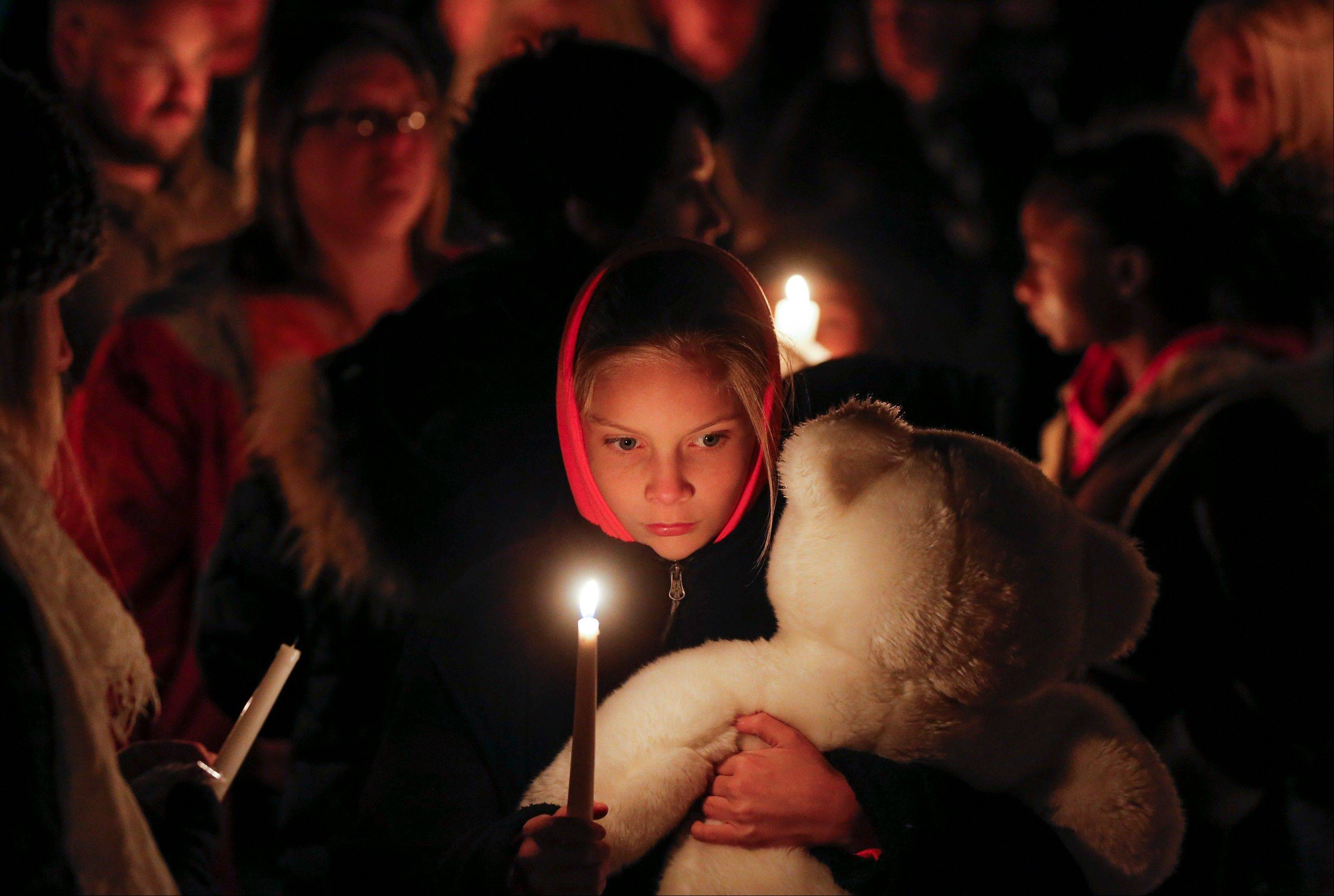 Lexi Umbarger clutches a teddy bear Wednesday during a candlelight vigil in Parsons, Kan., for Cami Umbarger and her three young children Hollie, Jaxon and Averie, who were found murdered in their Parsons home.