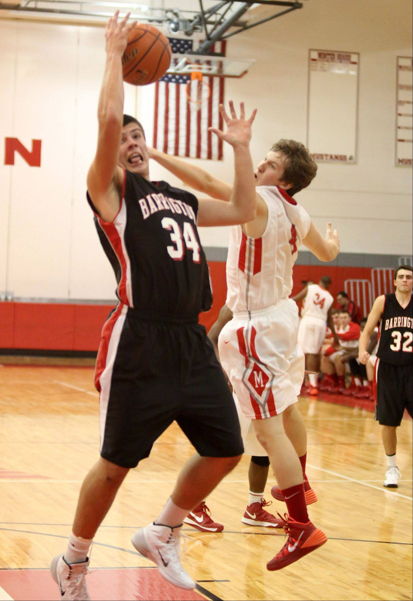 Barrington center Zach Bart pulls in an offensive rebound against Mundelein defender Sam Nelson in tournament play Friday at Mundelein.