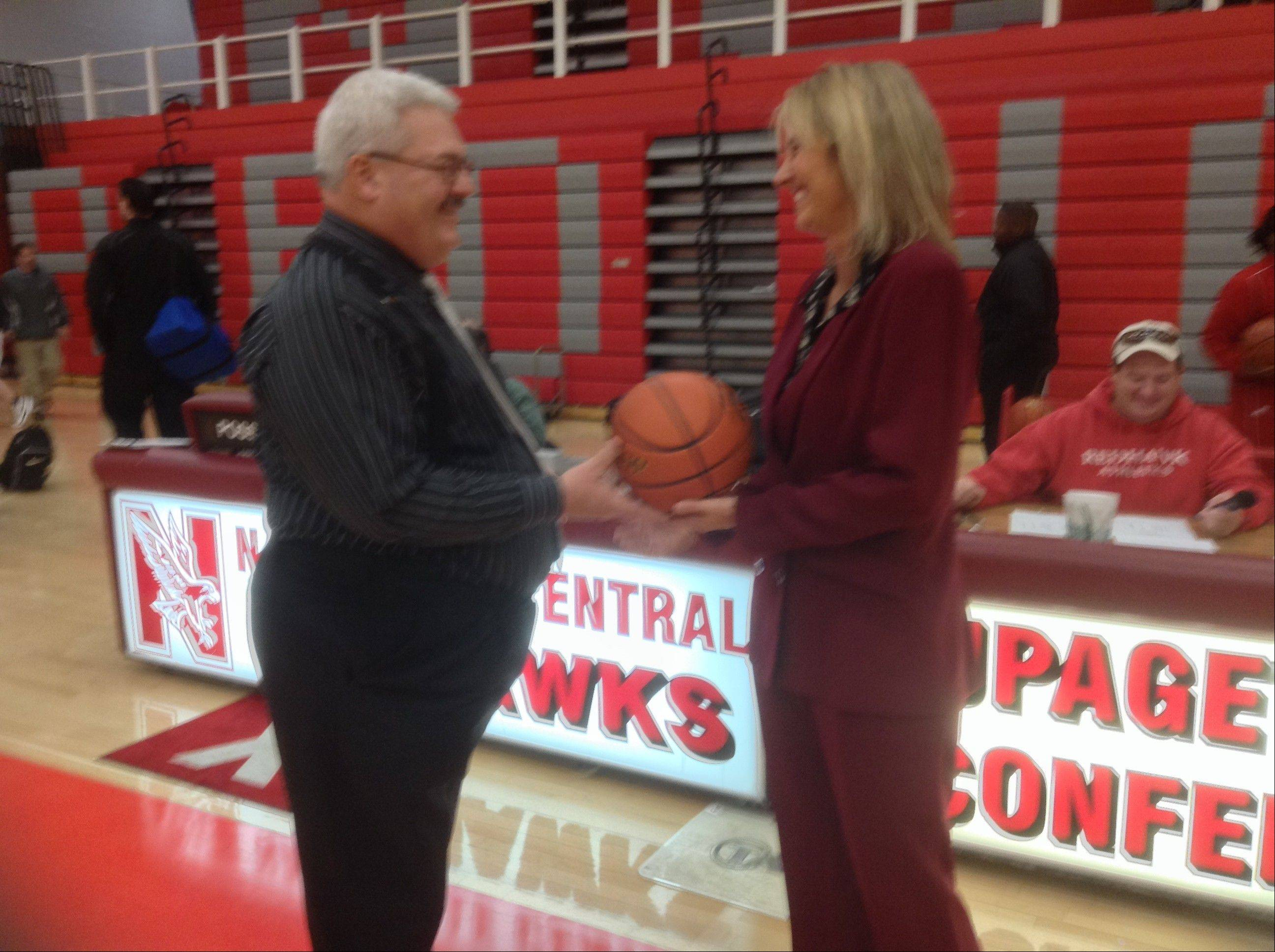 Naperville Central girls basketball coach Andy Nussbaum, left, presents Bartlett coach Denise Sarna the game ball Saturday after Sarna's Hawks beat Oswego East 52-49 in the Naperville Central/Benet Tip-Off Tournament. The win was the 300th of Sarna's career.