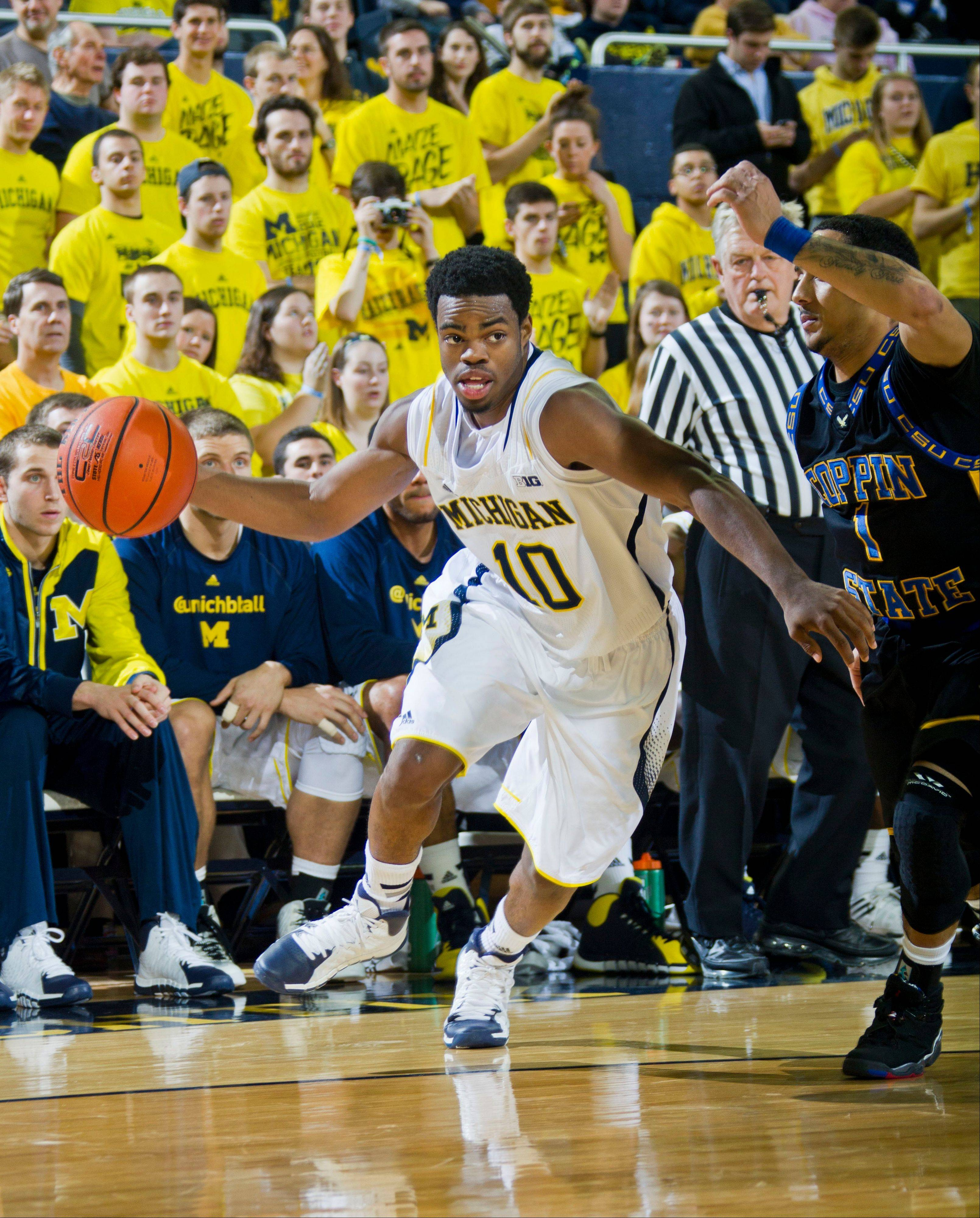 Michigan guard Derrick Walton Jr. dribbles up court against Coppin State guard Daquan Brickhouse, right, during the second half of Friday�s game at Crisler Center in Ann Arbor, Mich.