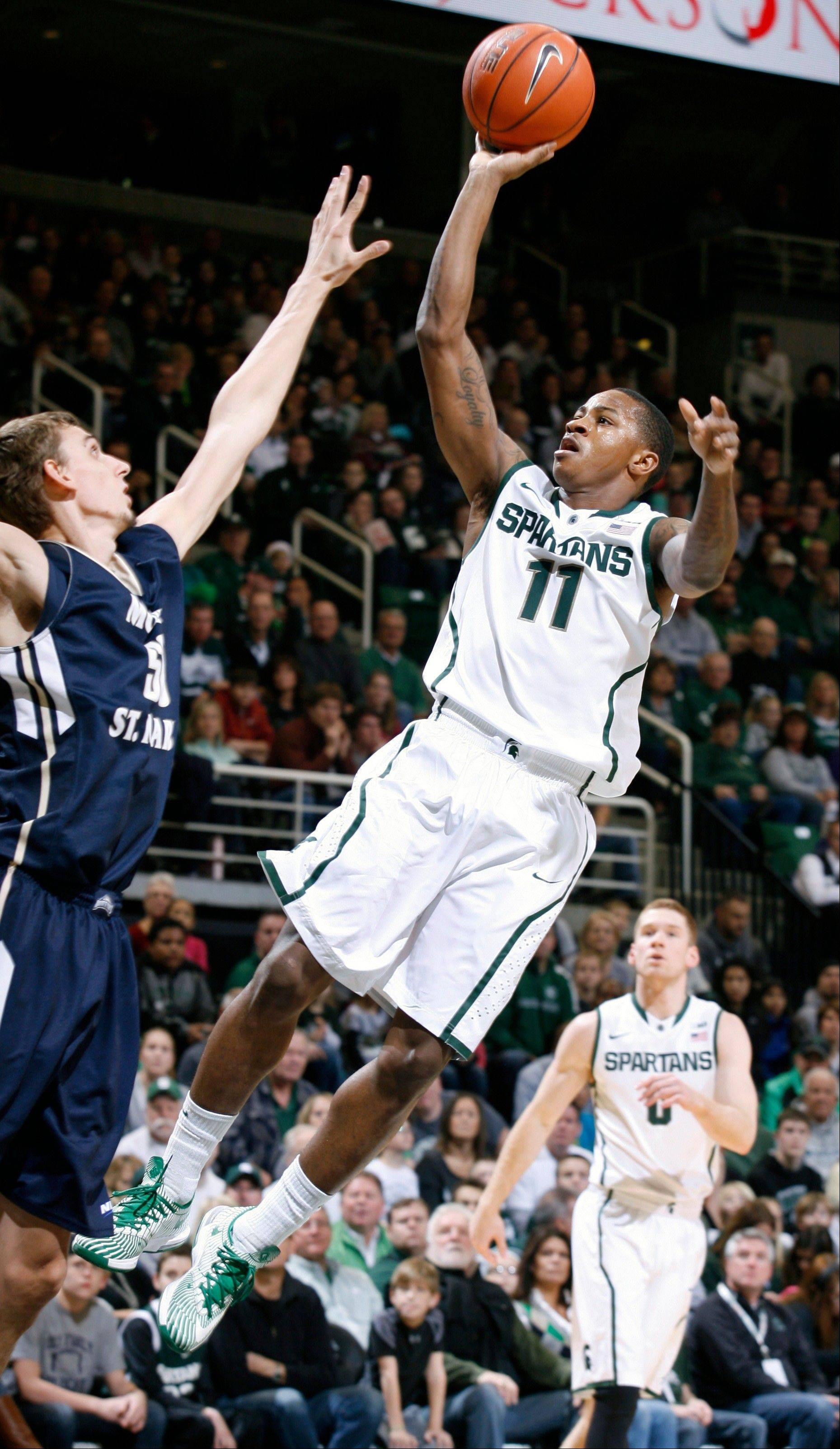 Michigan State's Keith Appling puts up a driving shot against Mount St. Mary's Taylor Danaher, left, during the first half of Friday's game in East Lansing, Mich.