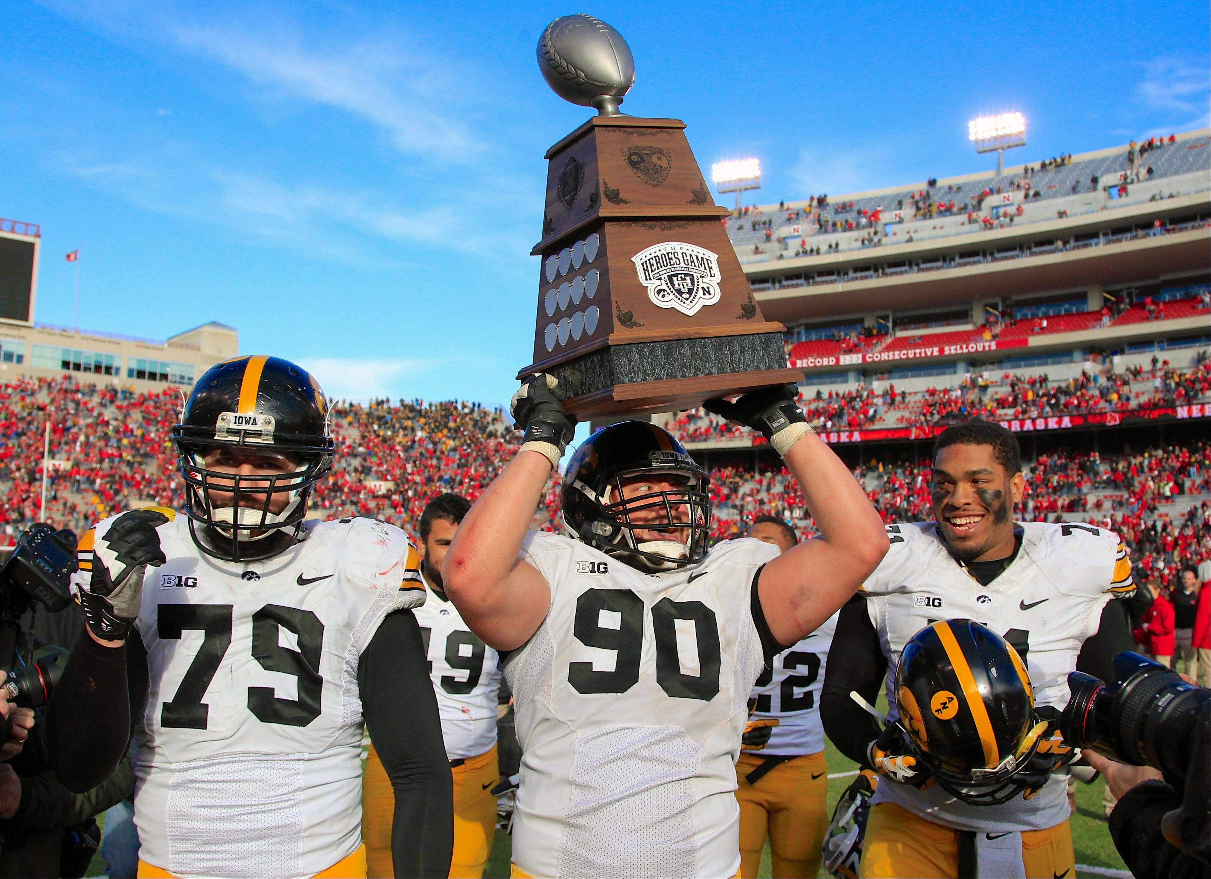 Iowa defensive lineman Louis Trinca-Pasat (90), flanked by teammates Dominic Alvis (79) and Carl Davis (71), hoists the Heroes Trophy after a win over Nebraska on Friday in Lincoln.