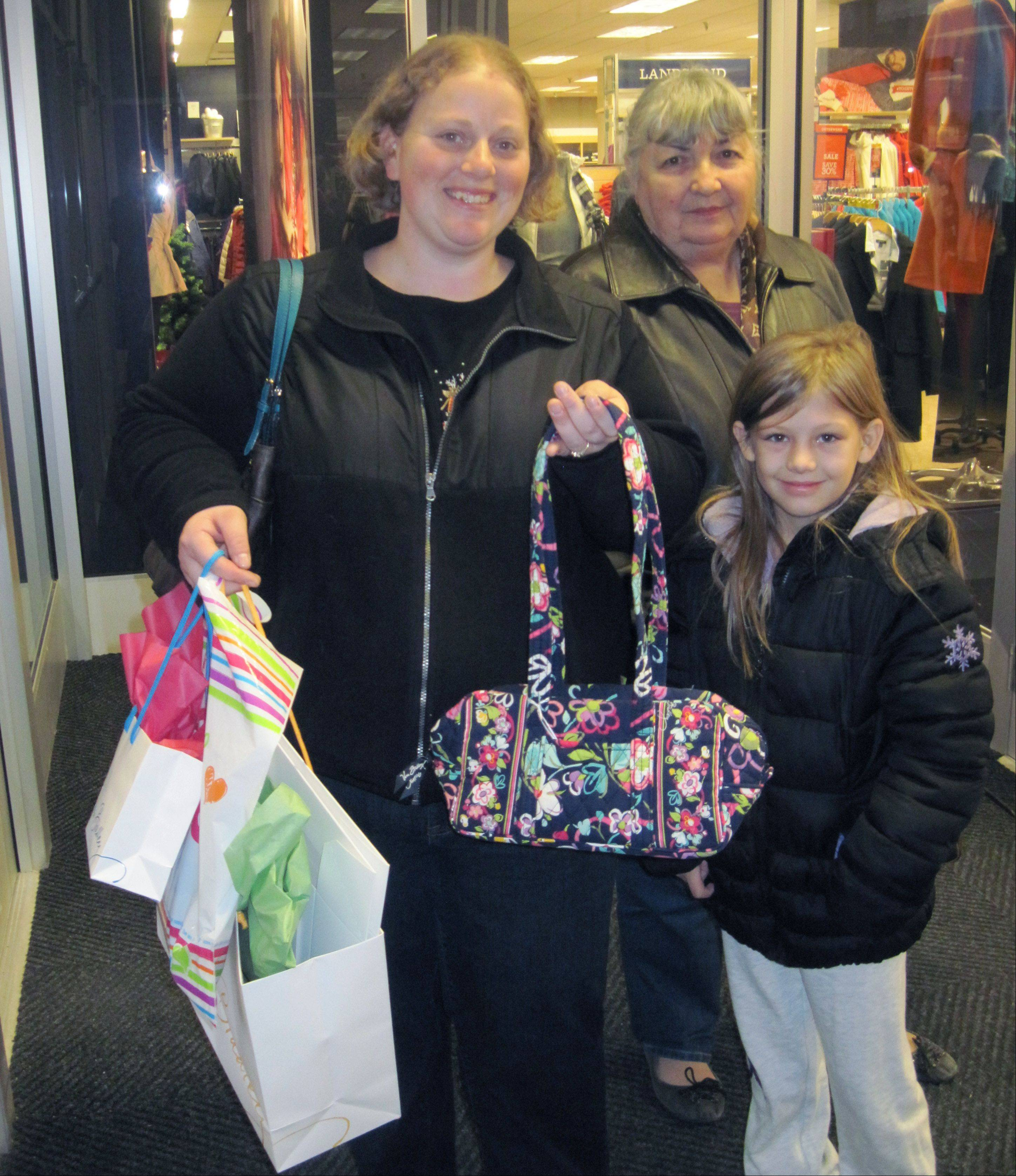 Marni Pyke/mpyke@dailyherald.comSarah Allen can't believe the deal she got on this Vera Bradley bag at Oakbrook Center Friday while out with her mother, Carol Fowler, and Fowler's granddaughter, Lilly, 9.