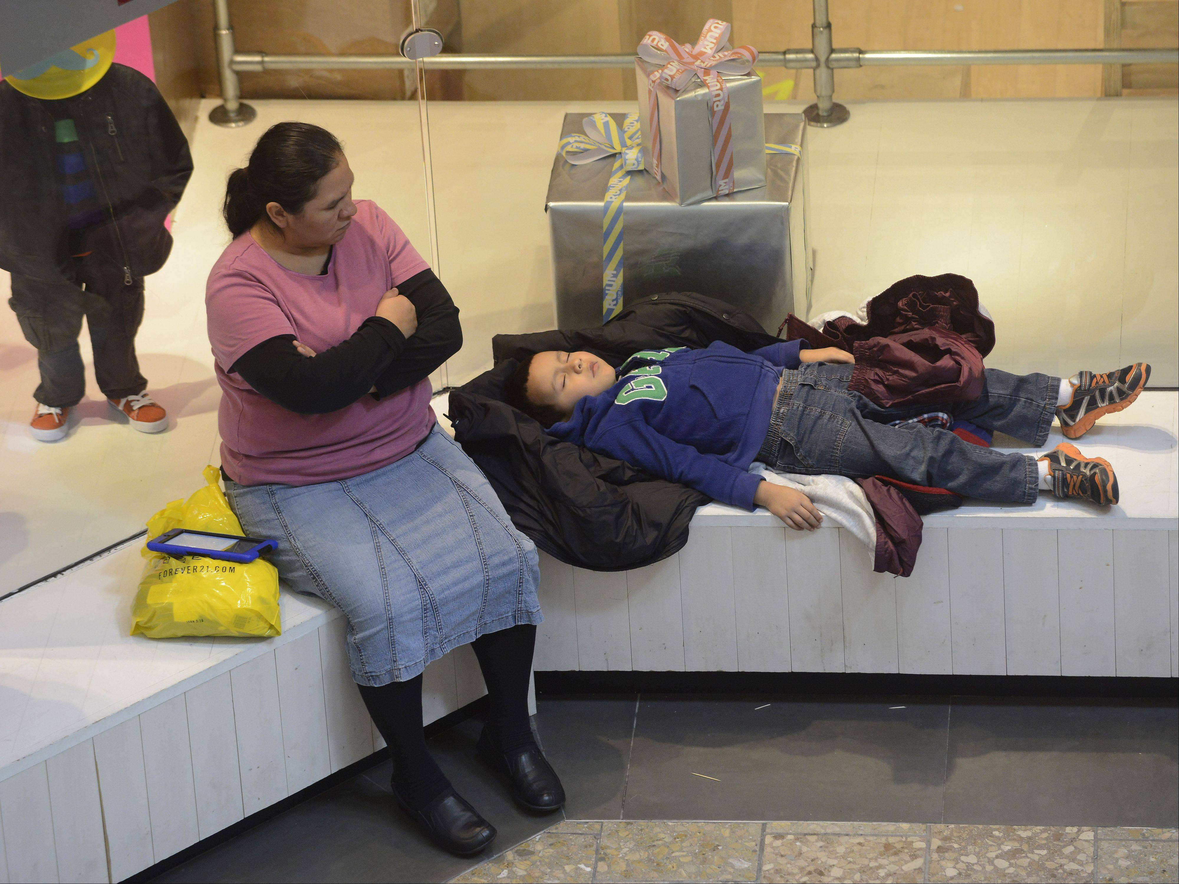 JOE LEWNARD/jlewnard@dailyherald.comSonia Estevane of Chicago gives her son Miguel, 5, a chance to rest while shopping Friday at Woodfield Mall in Schaumburg.