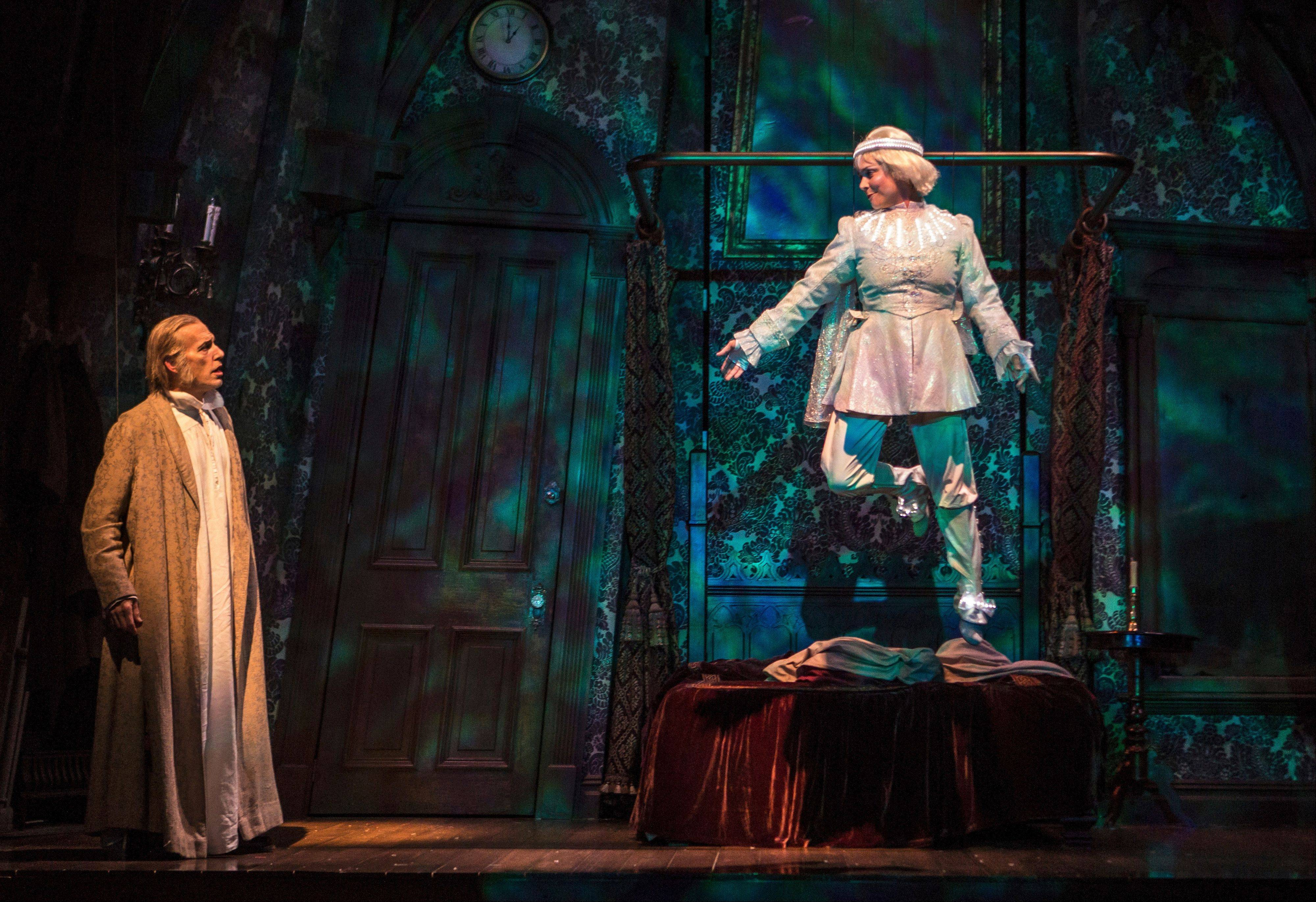 "Larry Yando, left, plays Ebenezer Scrooge and Elizabeth Ledo plays the Ghost of Christmas Past in Goodman Theatre's 36th annual production of ""A Christmas Carol."""