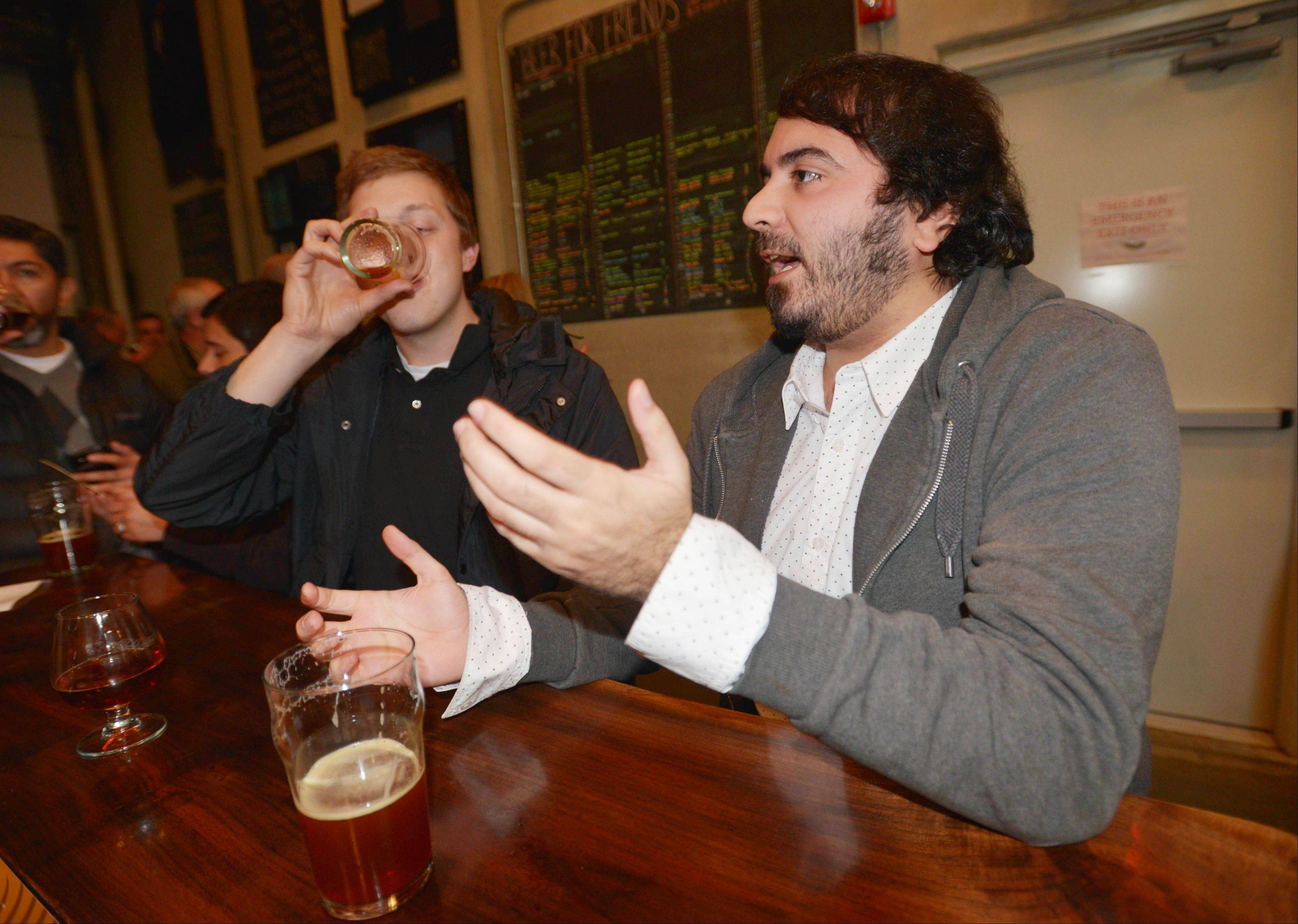 Anthony Collins, left, and Pouya Asadi, both of Aurora, enjoy beers at Solemn Oath Brewery in Naperville.
