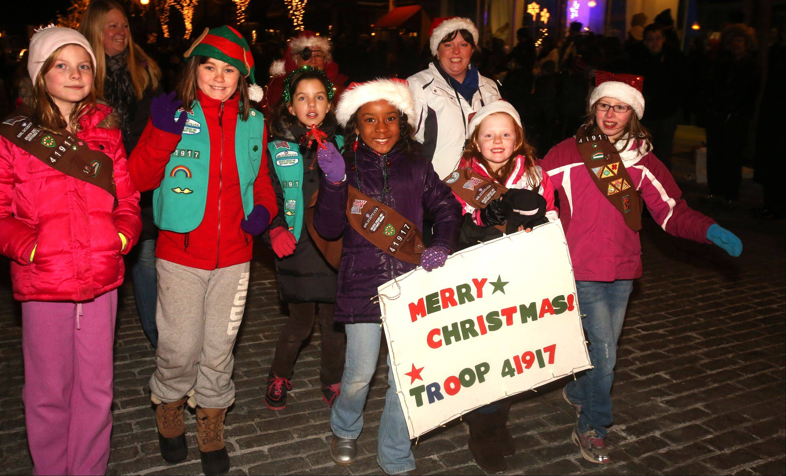 Daniel White/dwhite@dailyherald.comMembers of Girl Scout Troop 41917 of Hawthorne Elementary School march in the Wheaton Lighted Holiday Parade.