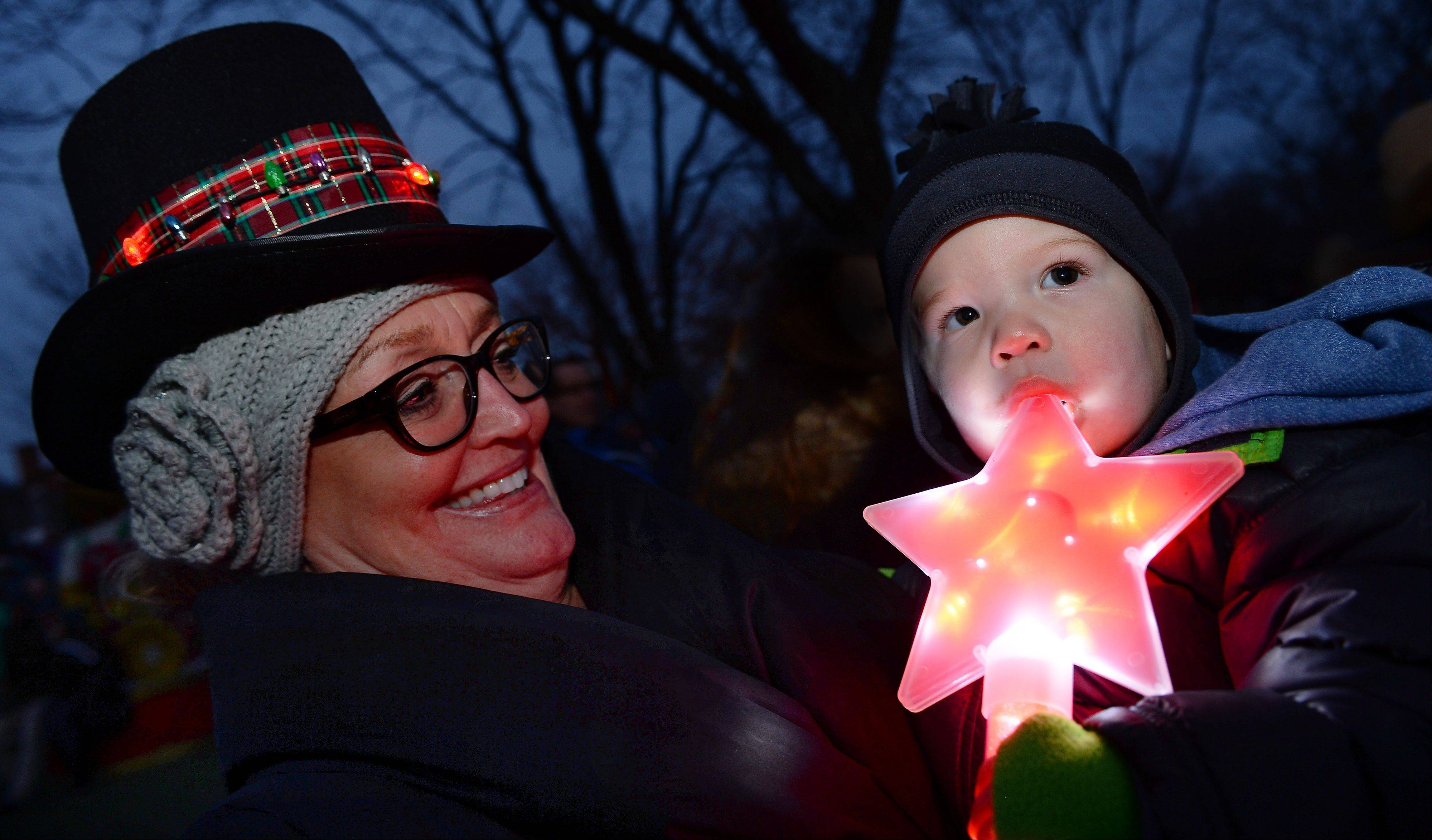 Dani Gresham of Inverness holds grandson Justin Mobley of Palatine as they wait for the lights to shine Friday at the annual tree-lighting ceremony at North School Park in Arlington Heights.