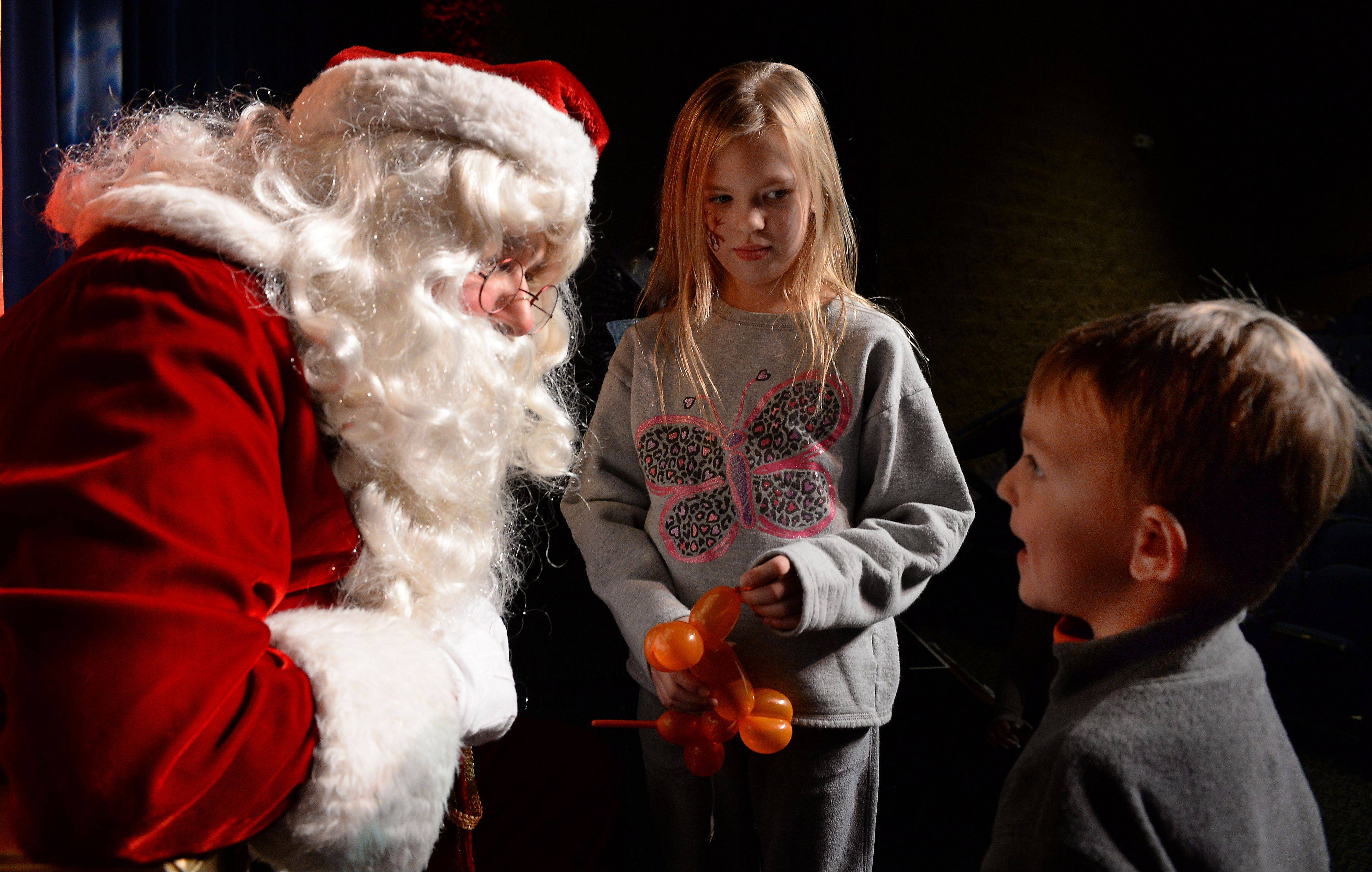 Santa arrived at the Prairie Center for the Arts in Schaumburg on Friday just in time to find out what Alexa Neis, 7, and her brother Evan, 4, wanted for Christmas.