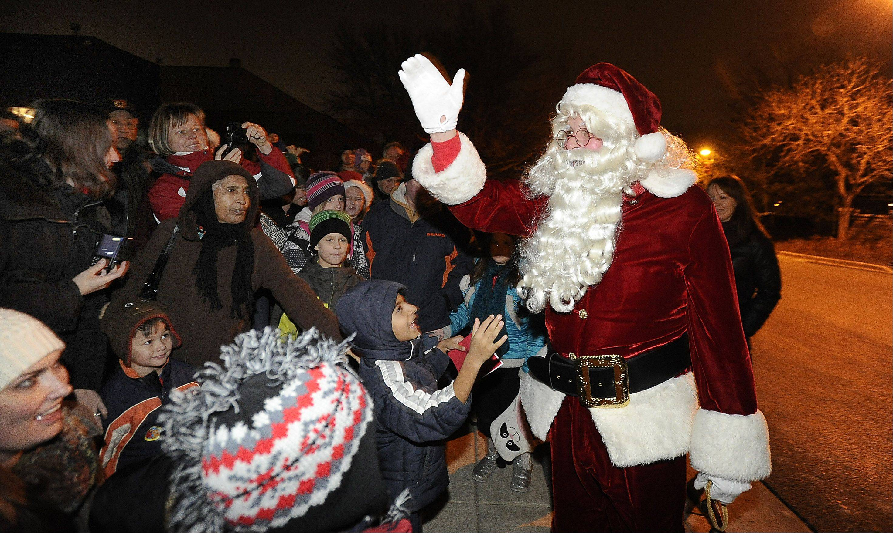 Santa put smiles on hundreds of kids' faces and listened to their Christmas wishes Friday night in Schaumburg.