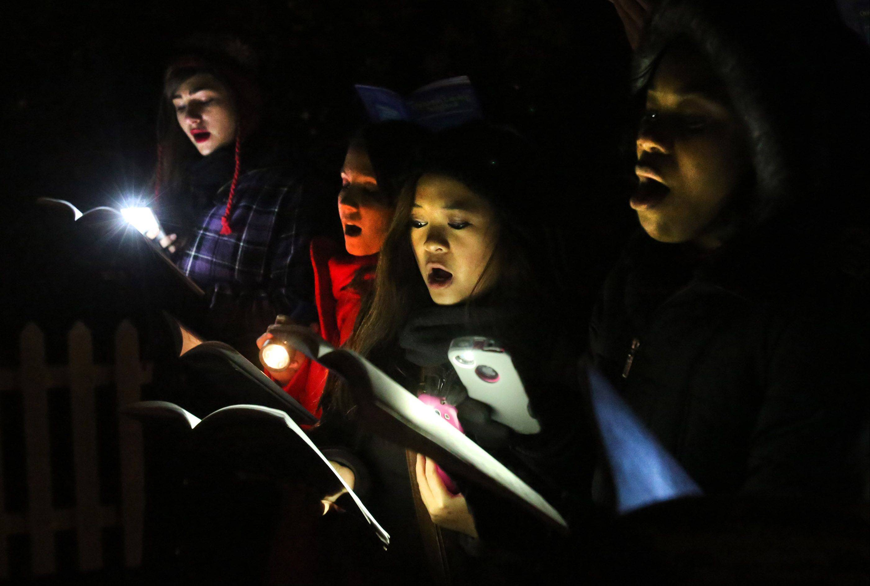 Sabrina O'Dowd, from left, Kaila Husk, Angelica Torres, Shiloh Lampkin and other members of the Round Lake High School group Mental Notes use their phones to light their music books as they sing Christmas songs during Round Lake Beach's tree-lighting event on Friday night.