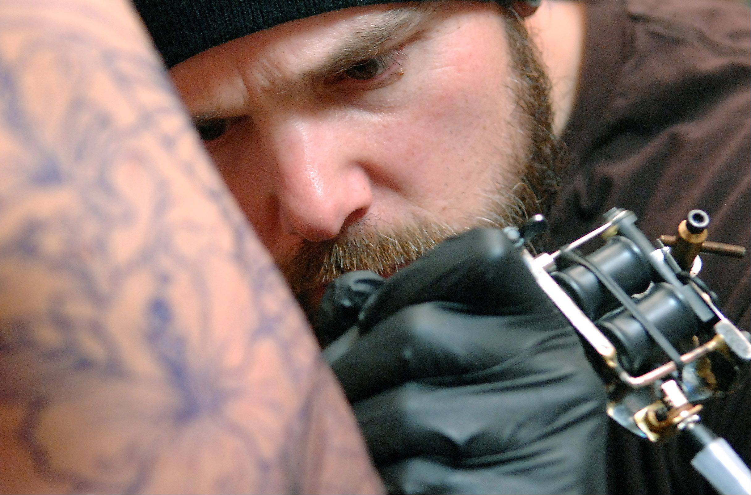 Artist Erik Thvedt of Top Notch Tattoos in Elgin works on the outline of a koi fish for Kyle Richardson of Bartlett. It's Richardson's first tattoo in 20 years so he didn't mind waiting the six months for an appointment with Thvedt.