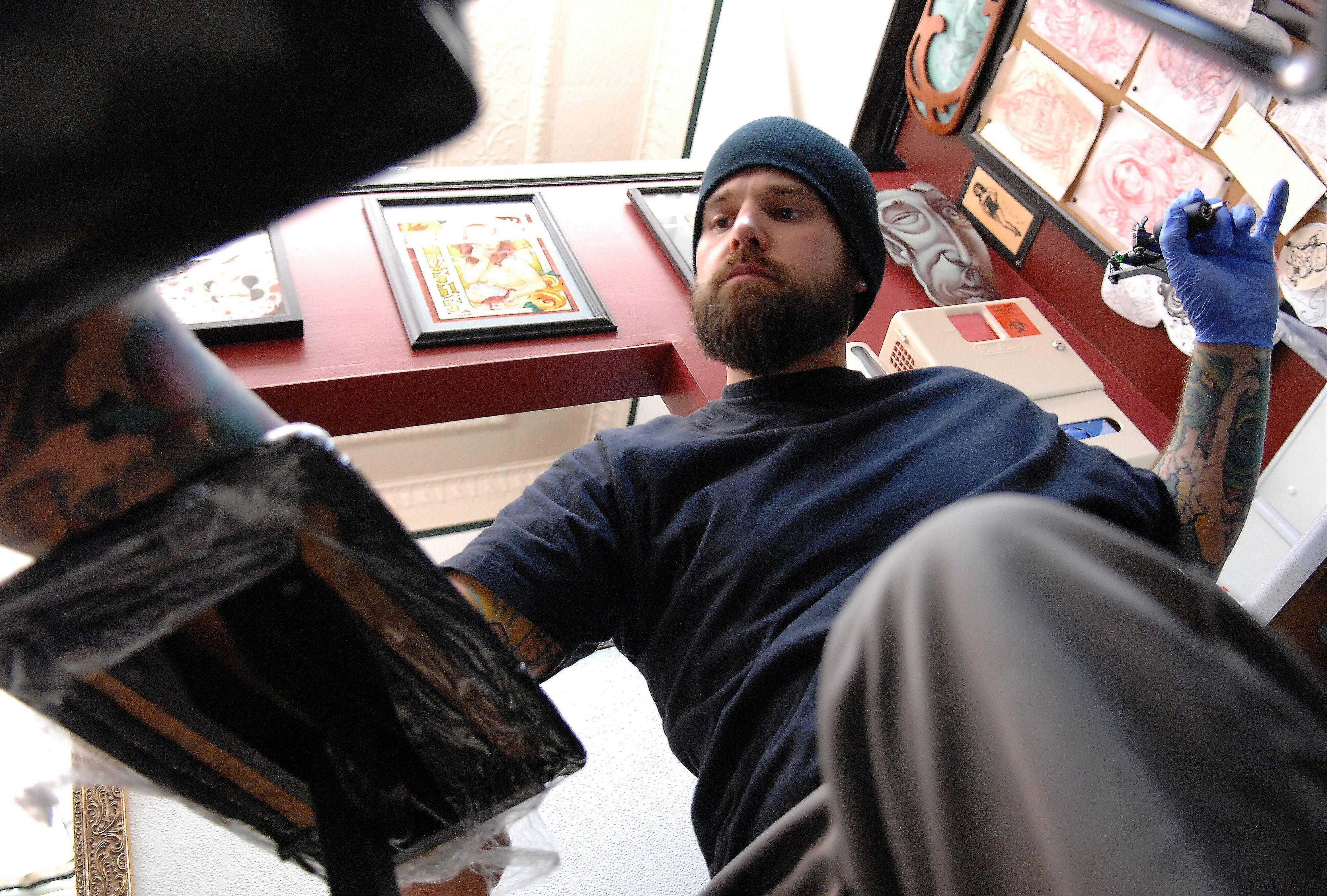 Tattoo artist Erik Thvedt pulls back to take a look at his work.