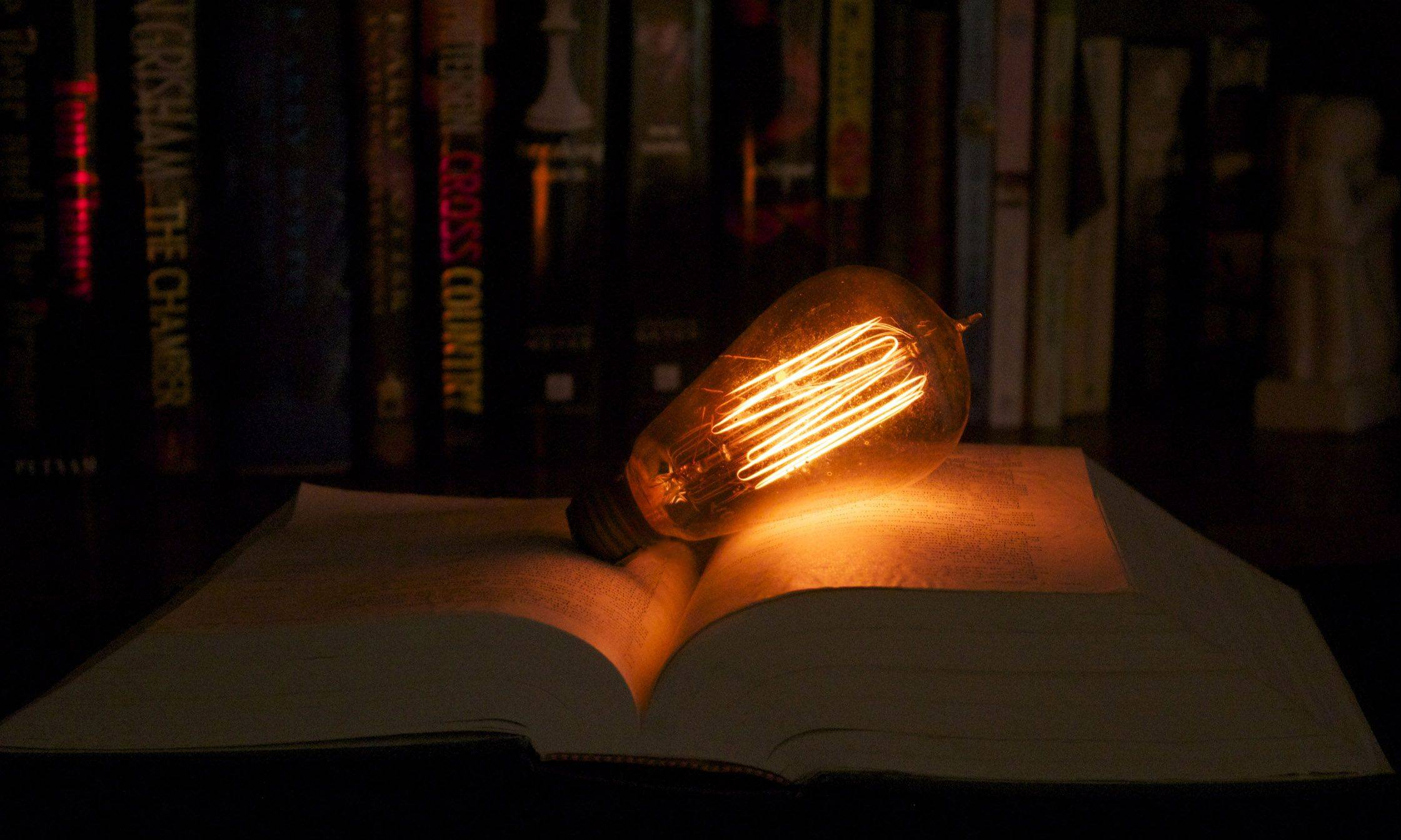The filaments of a very old light bulb glow as it is left on a book, powered using an 18-volt transformer.