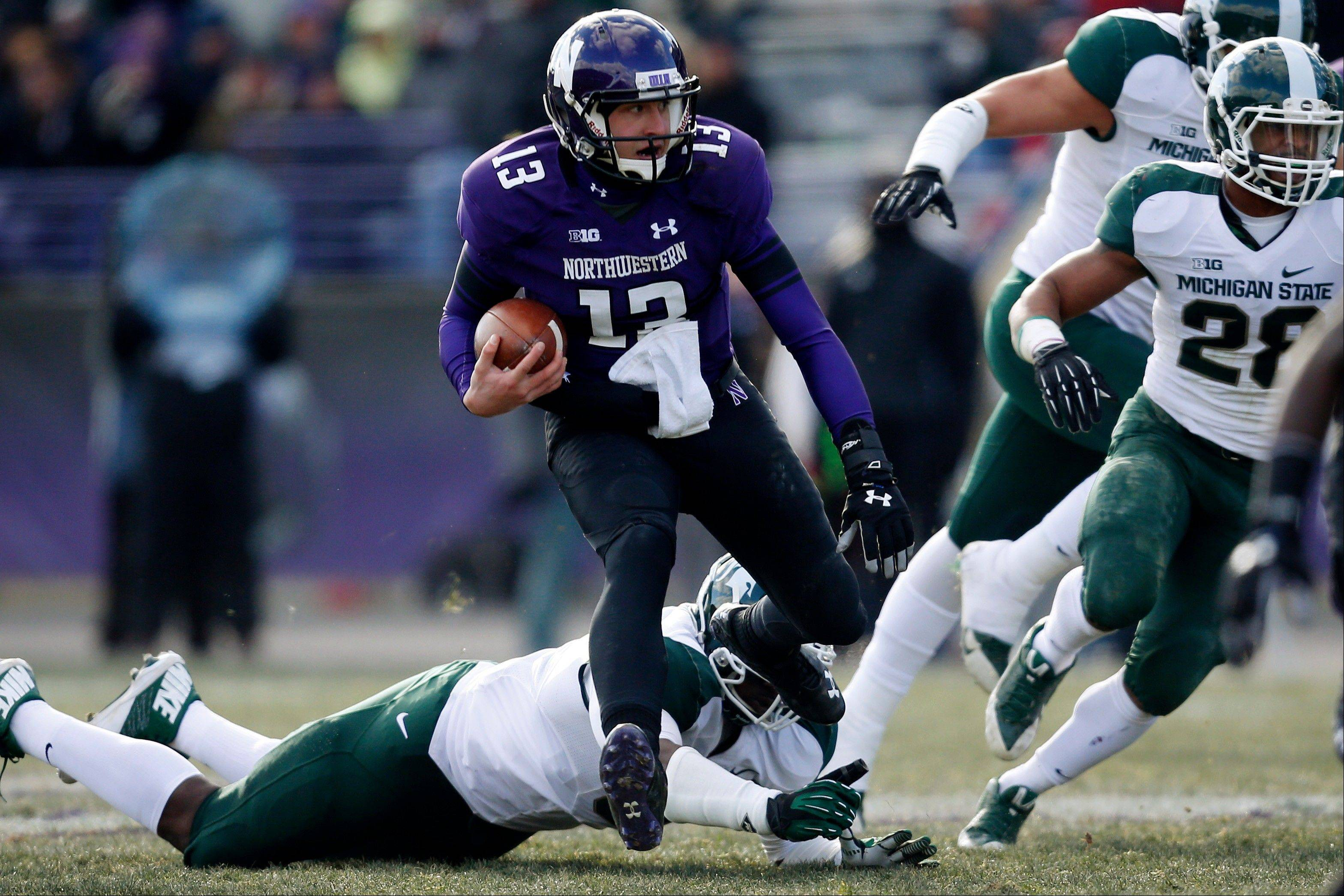 Northwestern quarterback Trevor Siemian (13) leaps over Michigan State defensive end Joel Heath (92) during the second half of an NCAA football game on Saturday, Nov. 23, 2013, in Evanston, Ill.