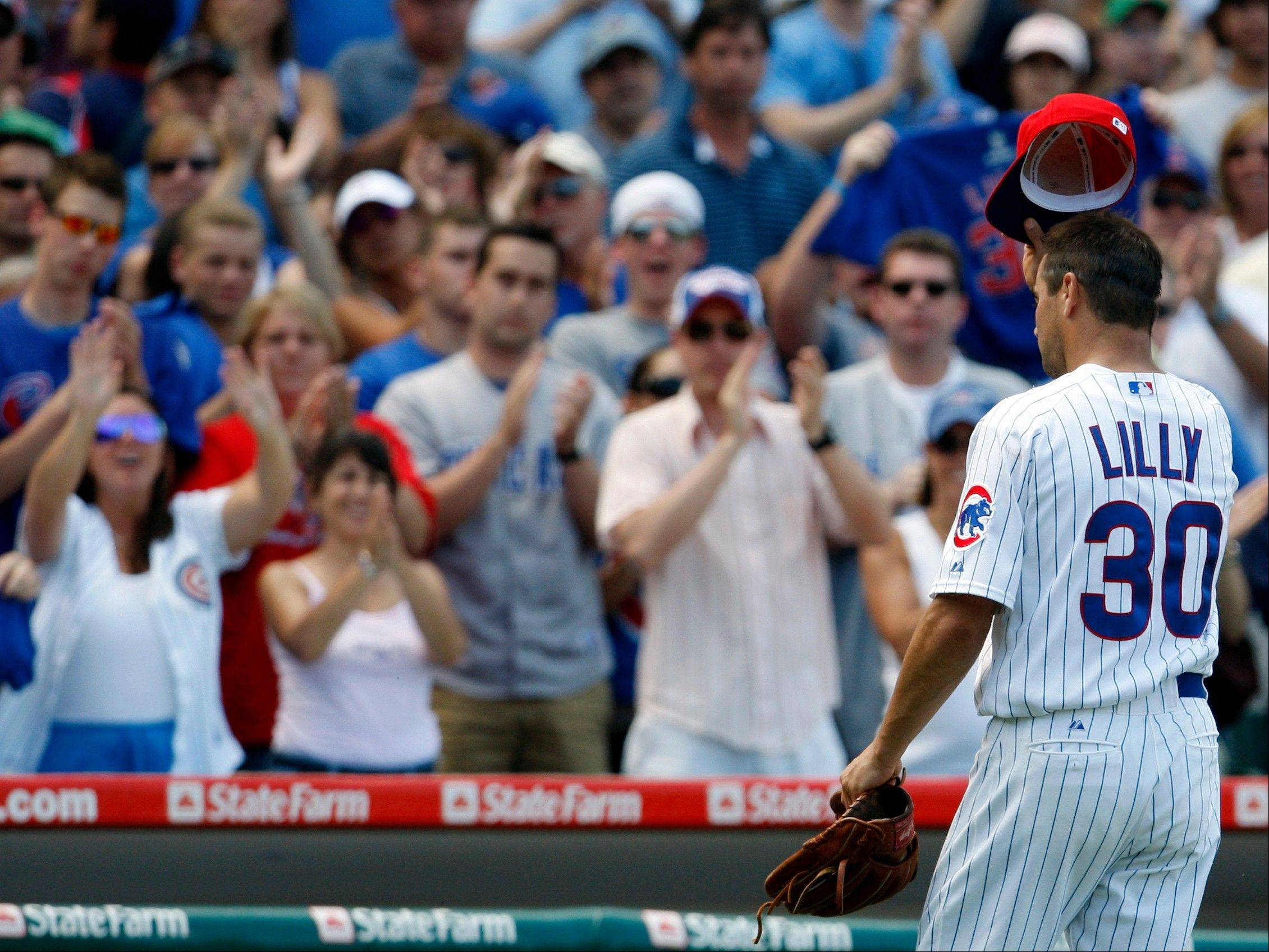 Chicago Cubs starter Ted Lilly tips his cap to the fans as he leaves the field during the seventh inning of a baseball game against the Milwaukee Brewers. Lilly announced his retirement from baseball on Friday because of a troublesome shoulder and back.