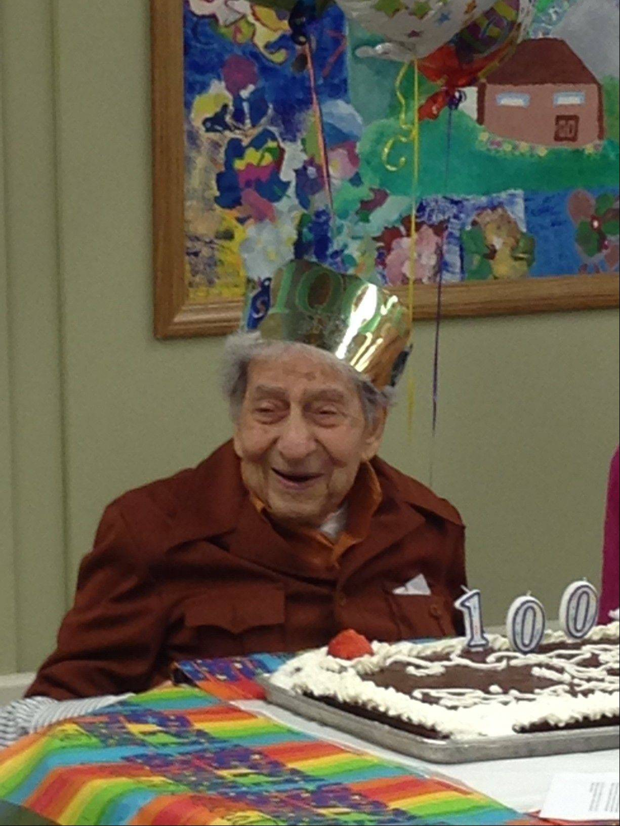 Meyer Marks of Mount Prospect blows out the candles on his 100th birthday cake.