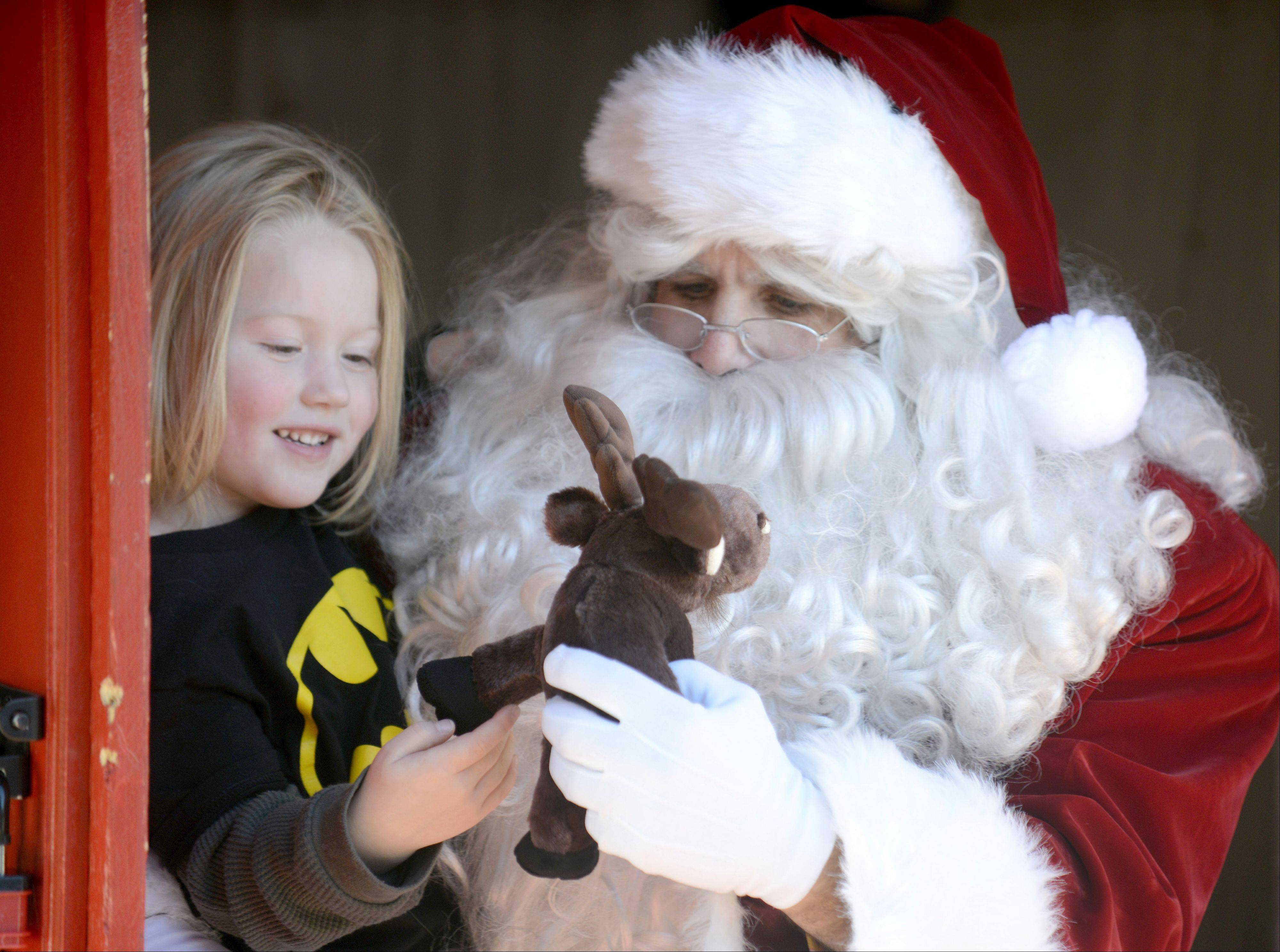 Maggy Kostiwa, 4, of Milwaukee asks Santa for a Batman cape for her moose (to match her shirt) while visiting him Saturday in the First Street Plaza during the St. Charles Holiday Homecoming festivities. Maggy�s father, Wade, grew up in St. Charles and was visiting relatives and friends over Thanksgiving. Santa was portrayed by Bill Watson of Lisle. His wife, Shannon, the executive director of the Tri City Health Partnership, was Mrs. Claus.