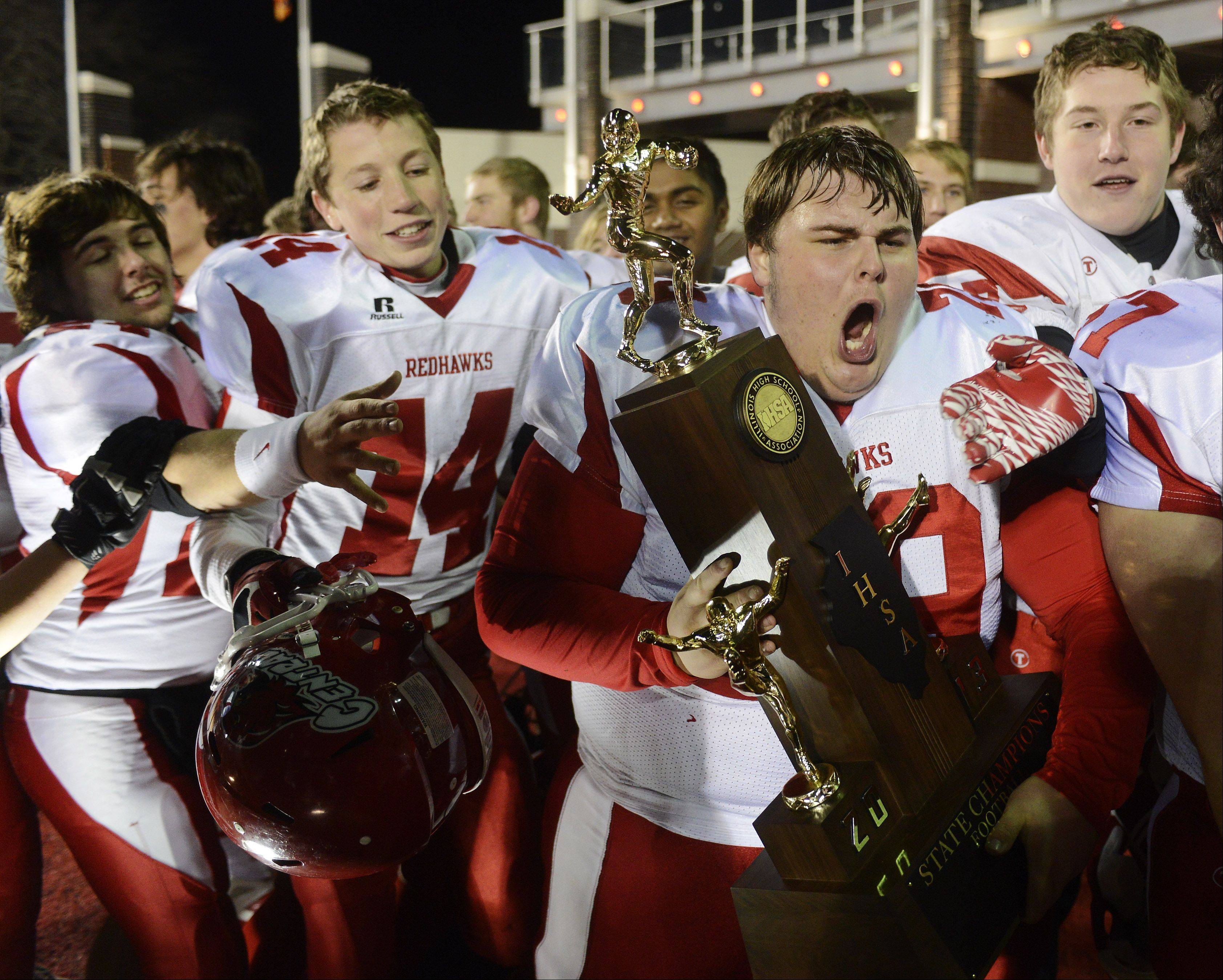 Naperville Central�s Chris Wenkel holds the team�s championship trophy after their victory over Loyola during the class 8A football final in DeKalb Saturday.