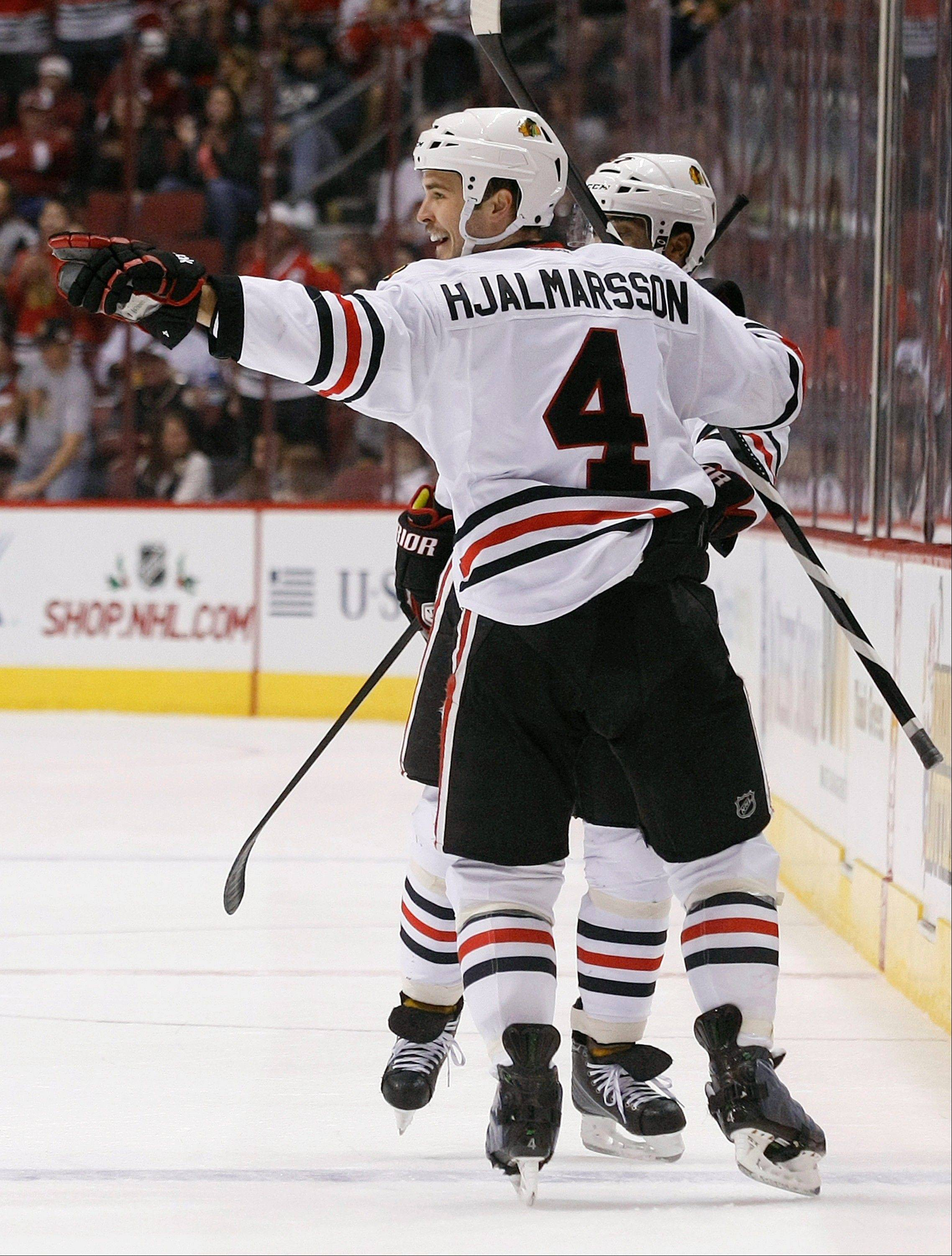 Chicago Blackhawks defenseman Niklas Hjalmarsson (4) celebrates after scoring a first period during an NHL hockey game against the Phoenix Coyotes on Saturday, Nov. 30, 2013, in Glendale, Ariz. (AP Photo/Rick Scuteri)