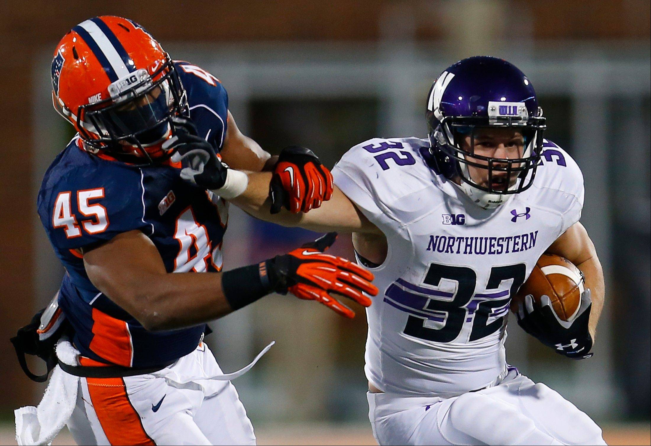 Northwestern running back Mike Trumpy (32) stiff arms Illinois linebacker Jonathan Brown (45) during the second half of an NCAA college football game on Saturday, Nov. 30, 2013, in Champaign, Ill. Northwestern won the game 37-34. (AP Photo/Jeff Haynes)