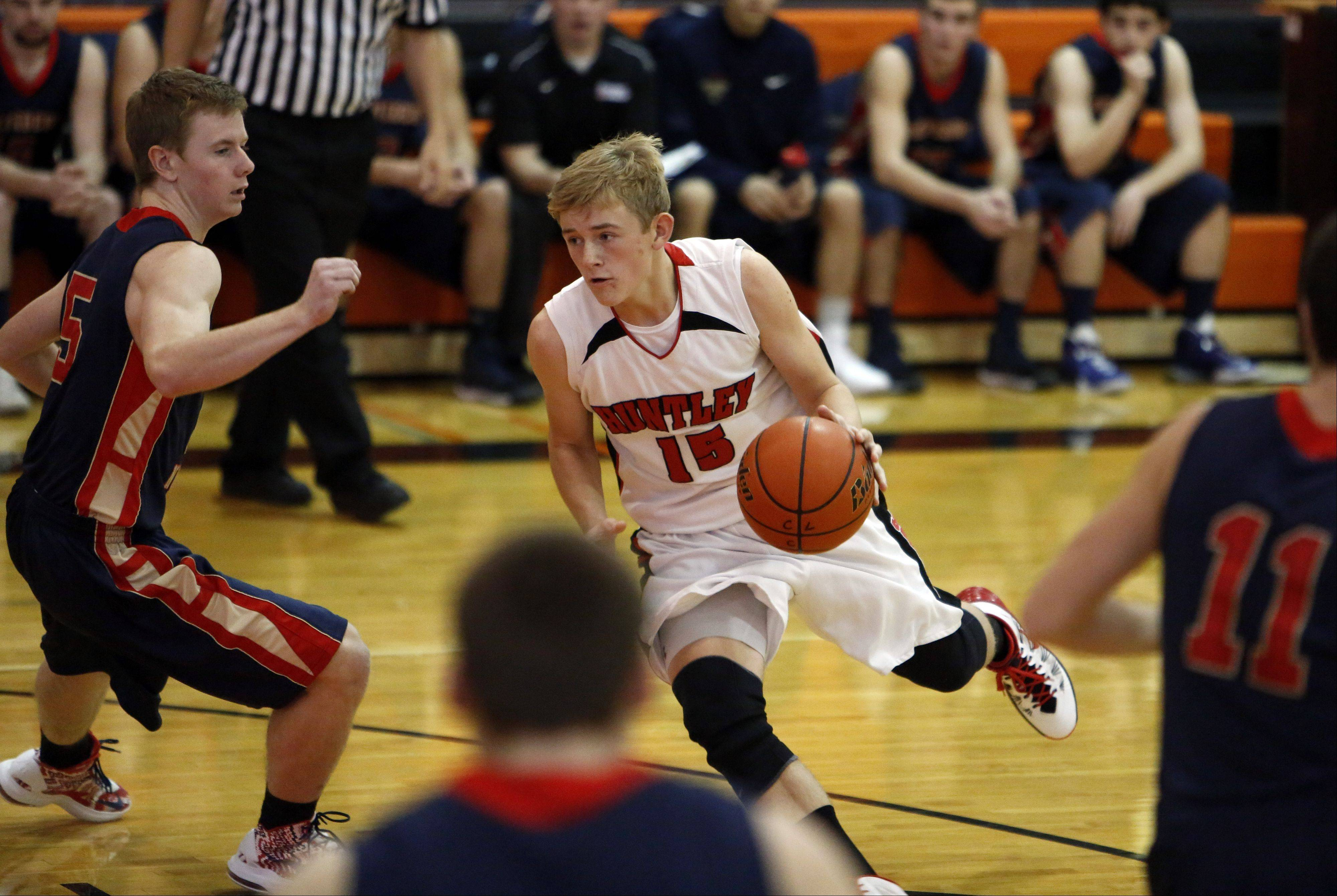 Huntley�s Jack Bessey drives to the hoop around Belvidere North�s Hunter Blake during the Crystal Lake Central High School Coaches vs, Cancer Thanksgiving Tourney Saturday in Crystal Lake.