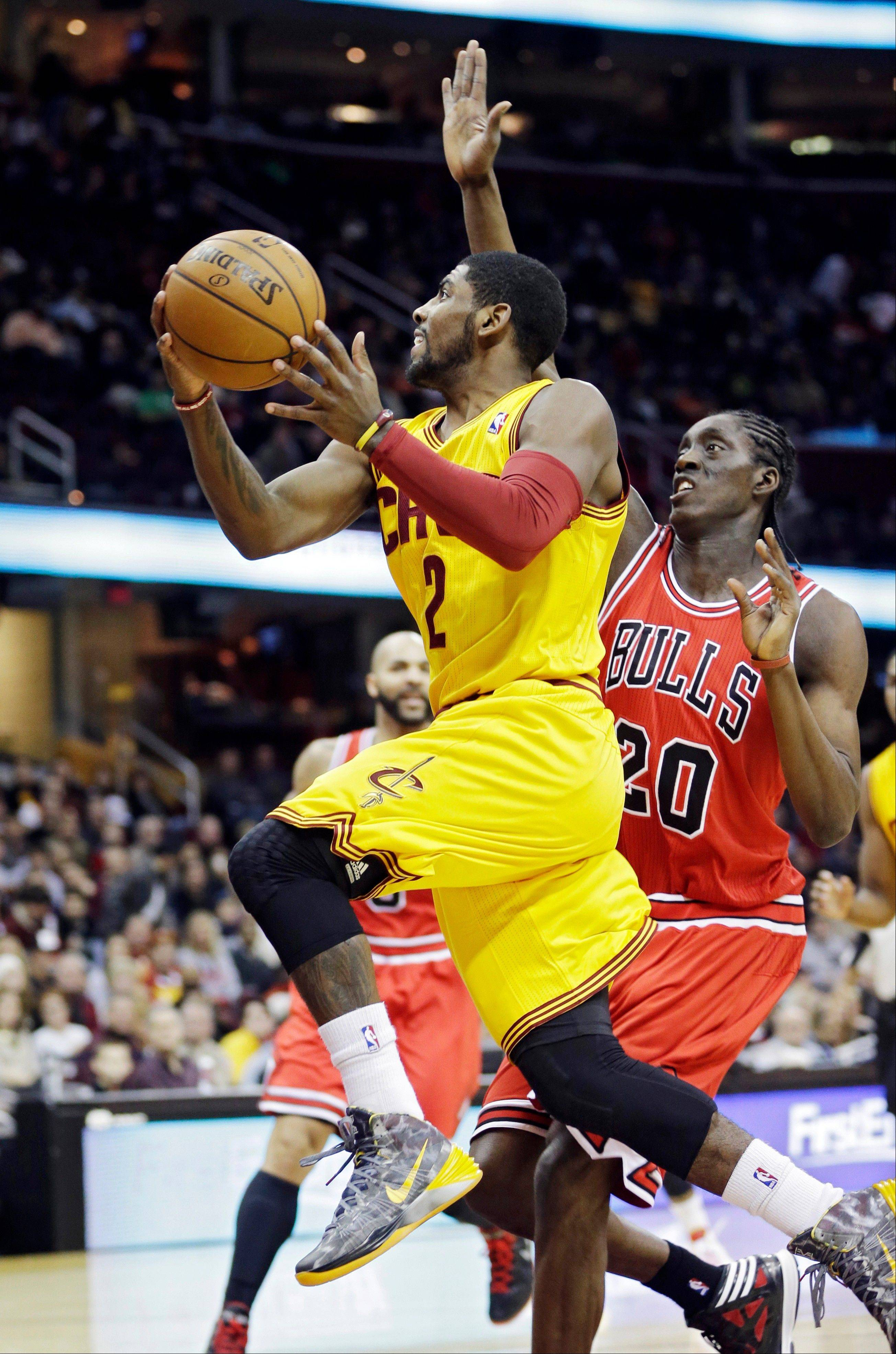 The Cavaliers' Kyrie Irving drives past Bulls rookie Tony Snell, who scored 13 of his 18 points in the second half to help the Bulls stage a comeback.